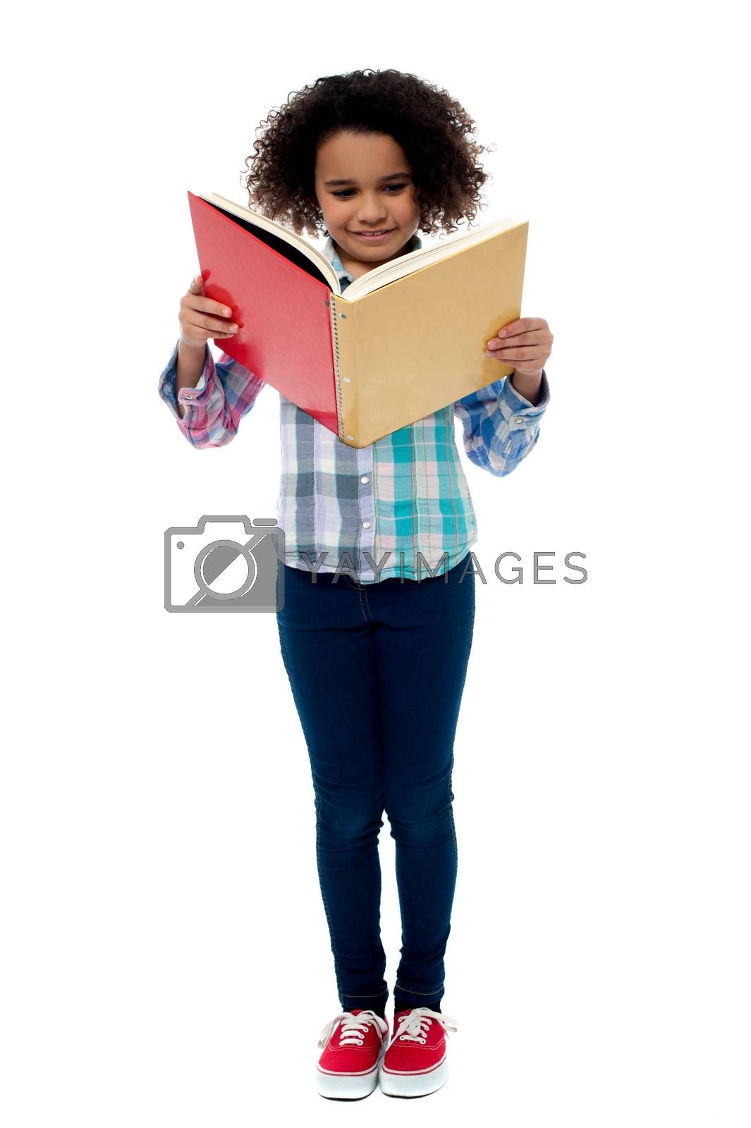 Full length image of school girl reading a book