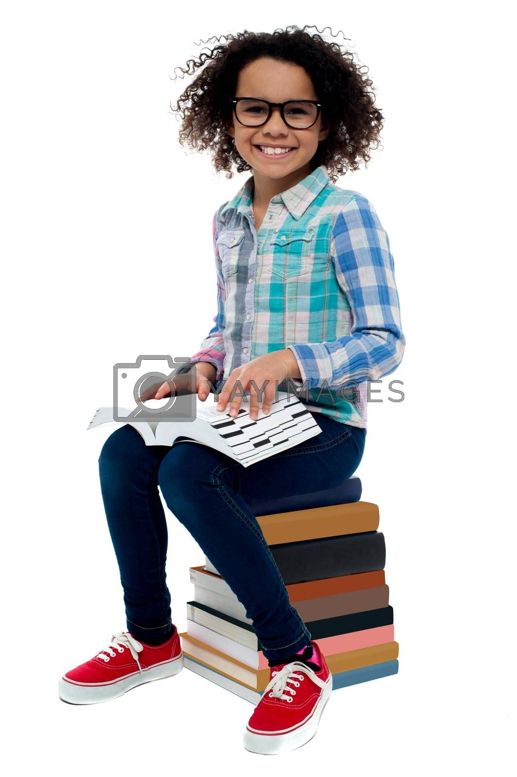 Happy girl sitting on stack of books over white