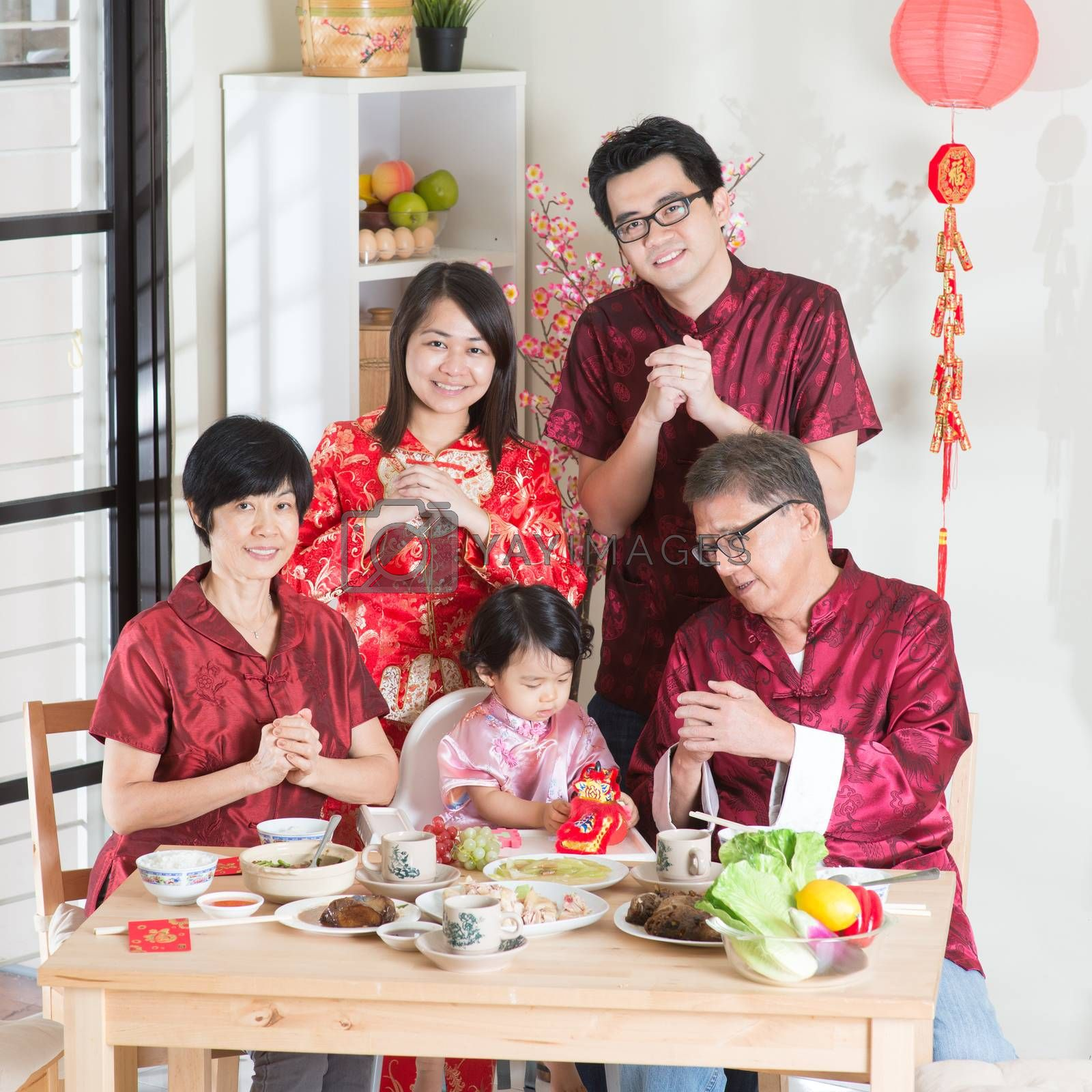 Spring seasons Chinese New Year, reunion dinner. Happy Asian Chinese multi generation family with red cheongsam greeting while dining at home.