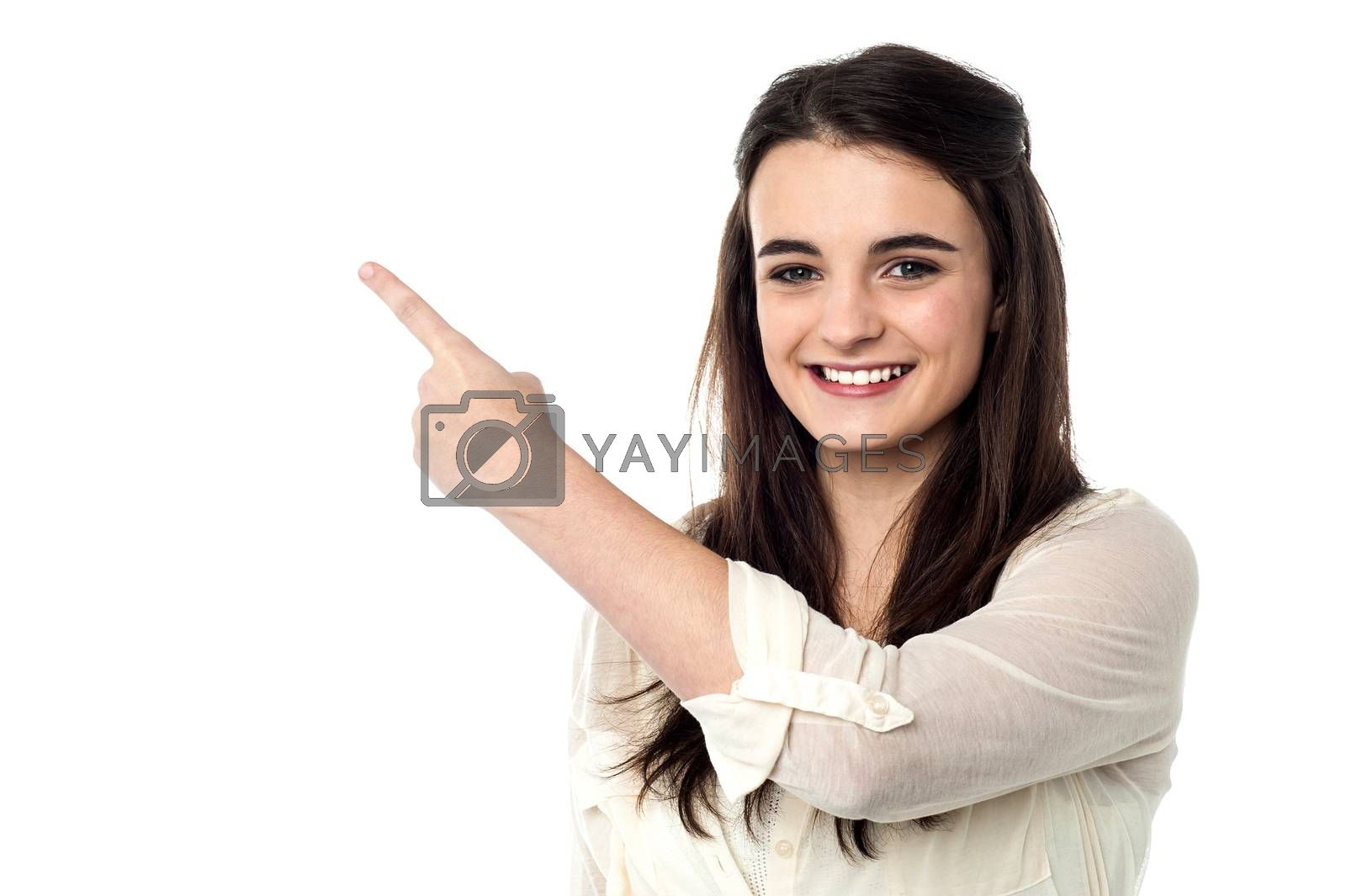Pretty girl pointing at copy space area