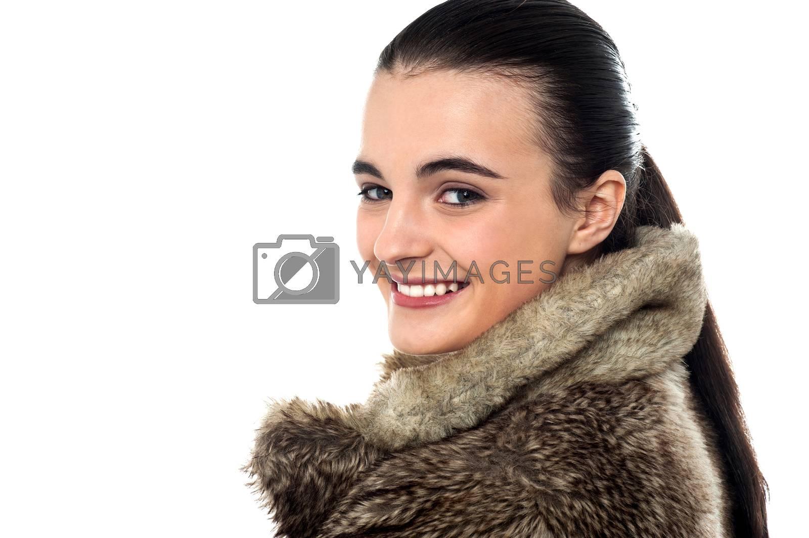 Teen girl in fur jacket, looking over shoulder