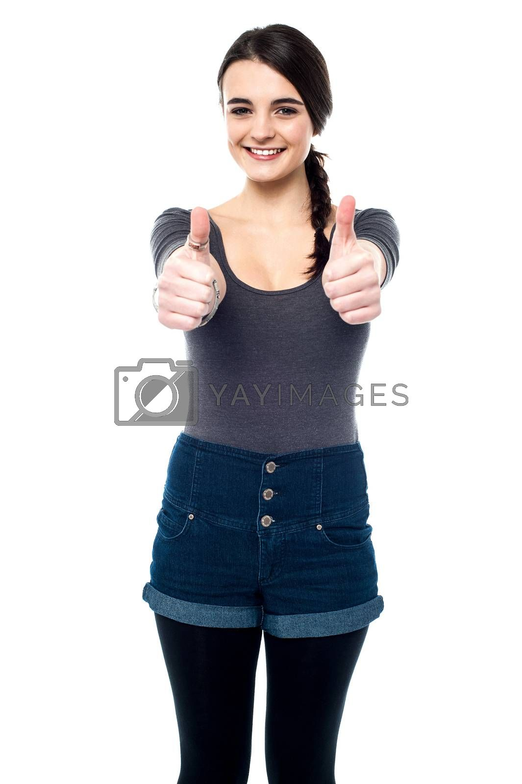 Teen girl making thumbs up gesture by two hands