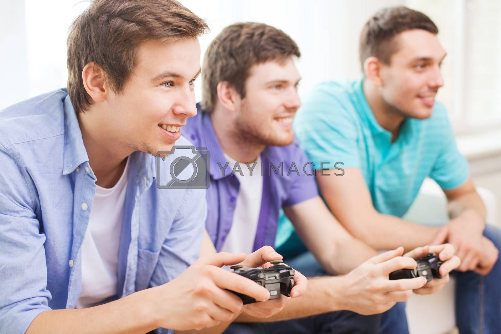 smiling friends playing video games at home by dolgachov