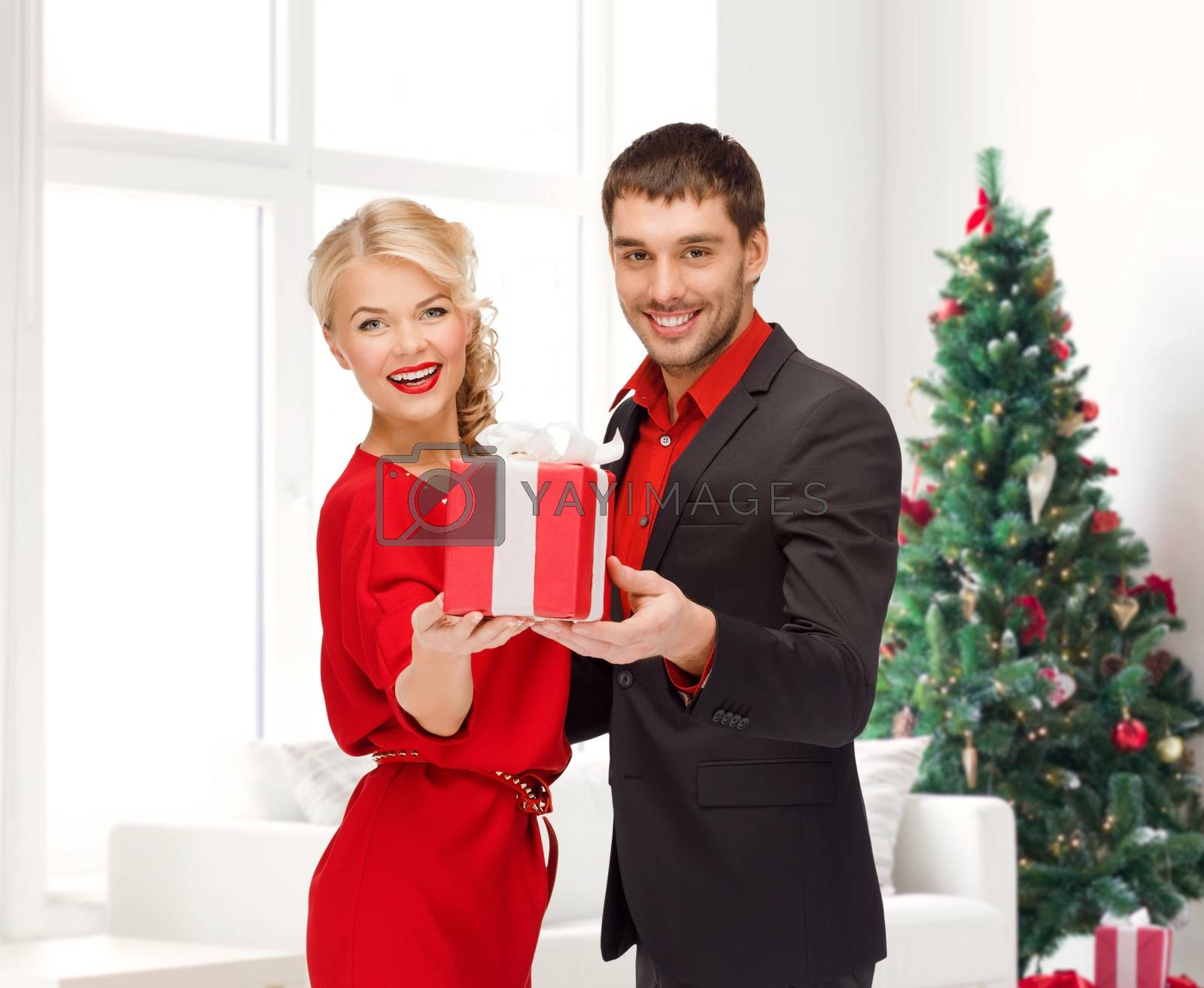 christmas, holidays, valentine's day, celebration and people concept - smiling man and woman with present over living room and christmas tree background