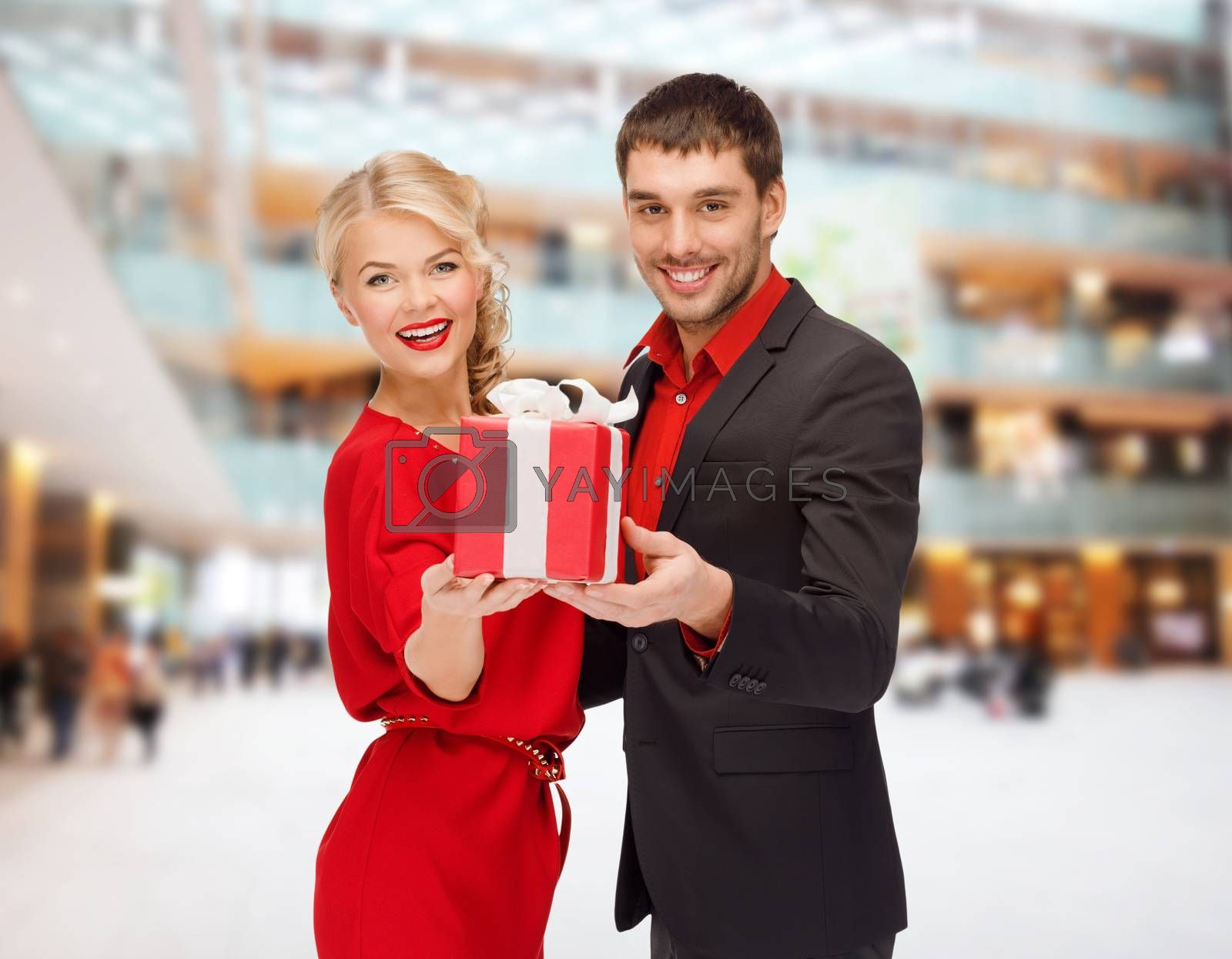 christmas, holidays, valentine's day, celebration and people concept - smiling man and woman with present over shopping centre background