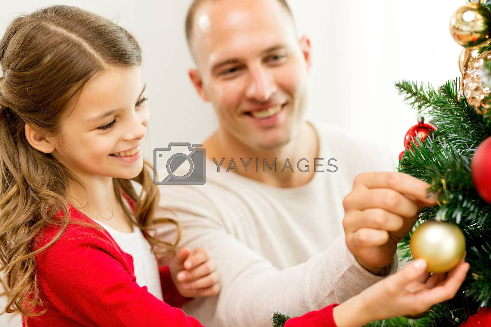 family, holidays, generation and people concept - smiling girl with father decorating christmas tree at home