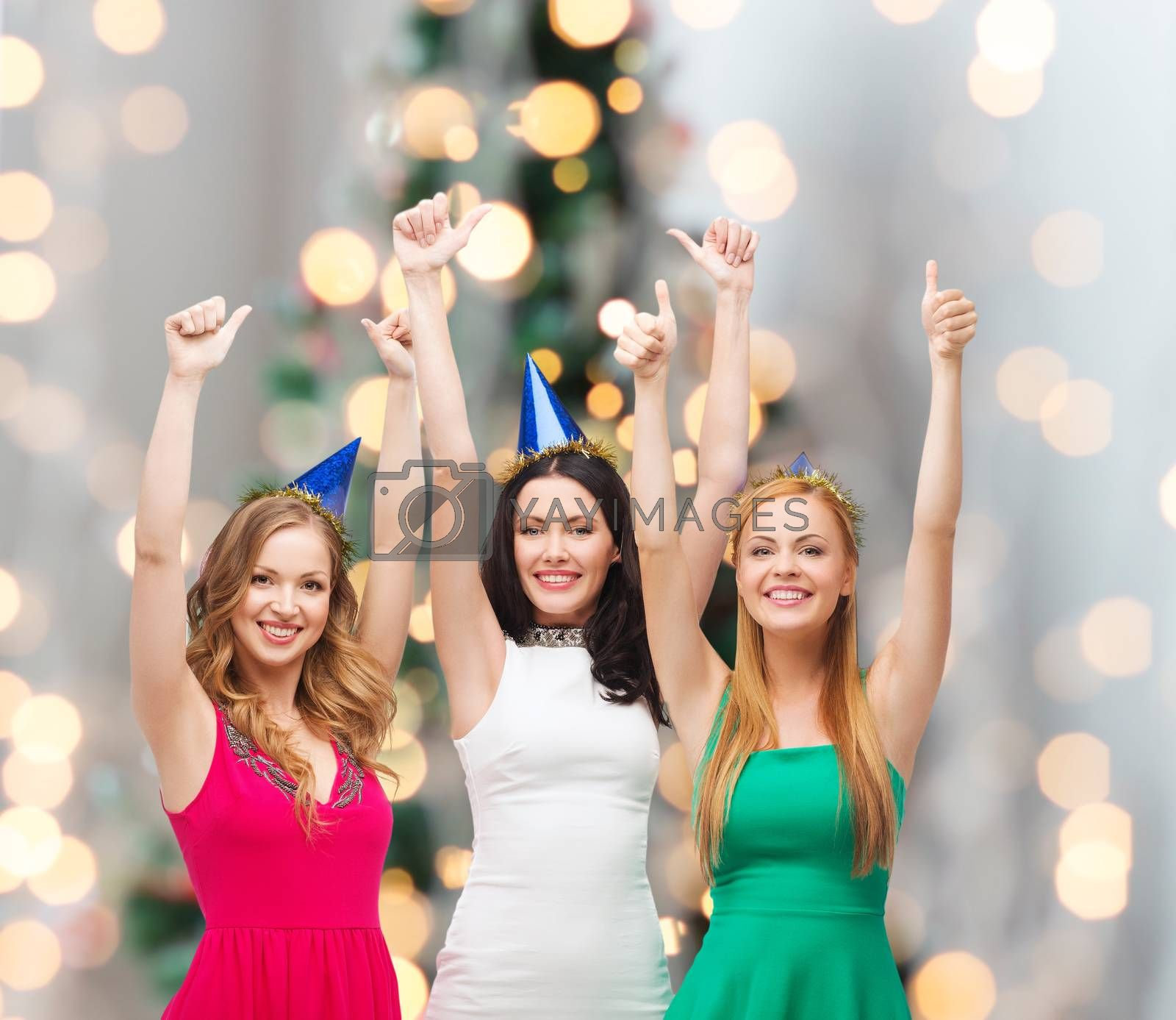 holidays, people, gesture and celebration concept - smiling women in party caps showing thumbs up over christmas tree lights background