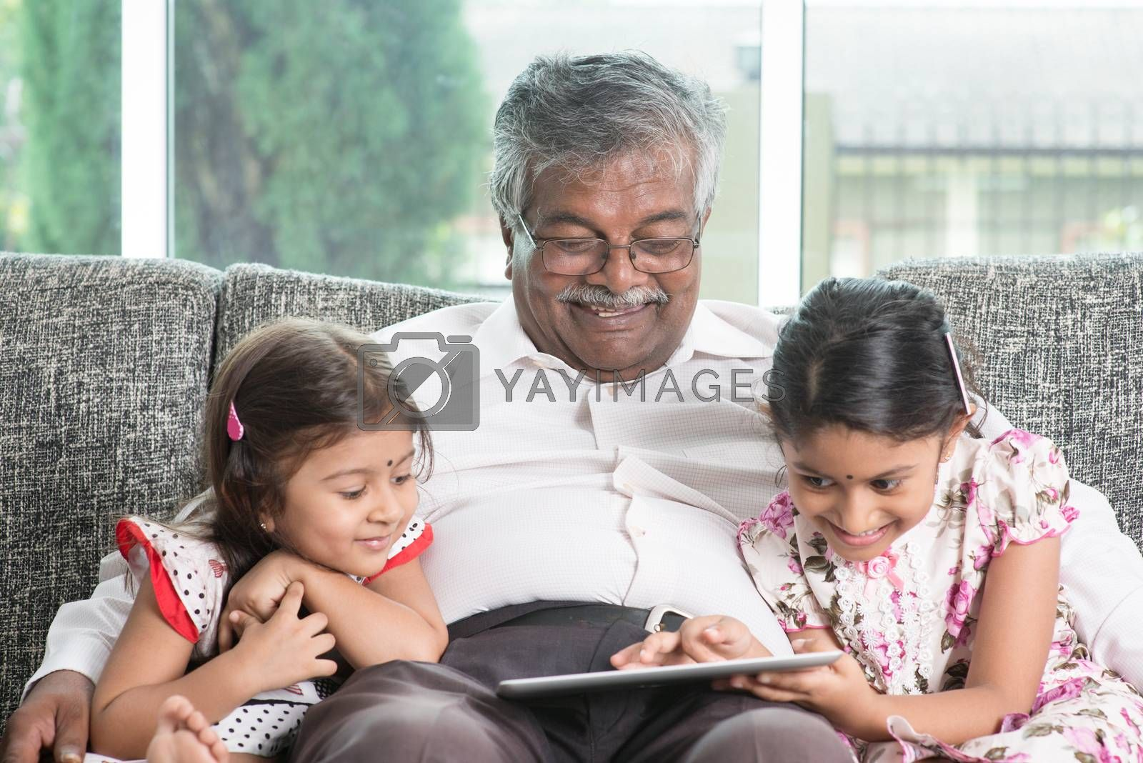Modern technology concept. Grandparent and grandchildren using touch screen tablet computer. Portrait Indian family at home. Asian people living lifestyle.