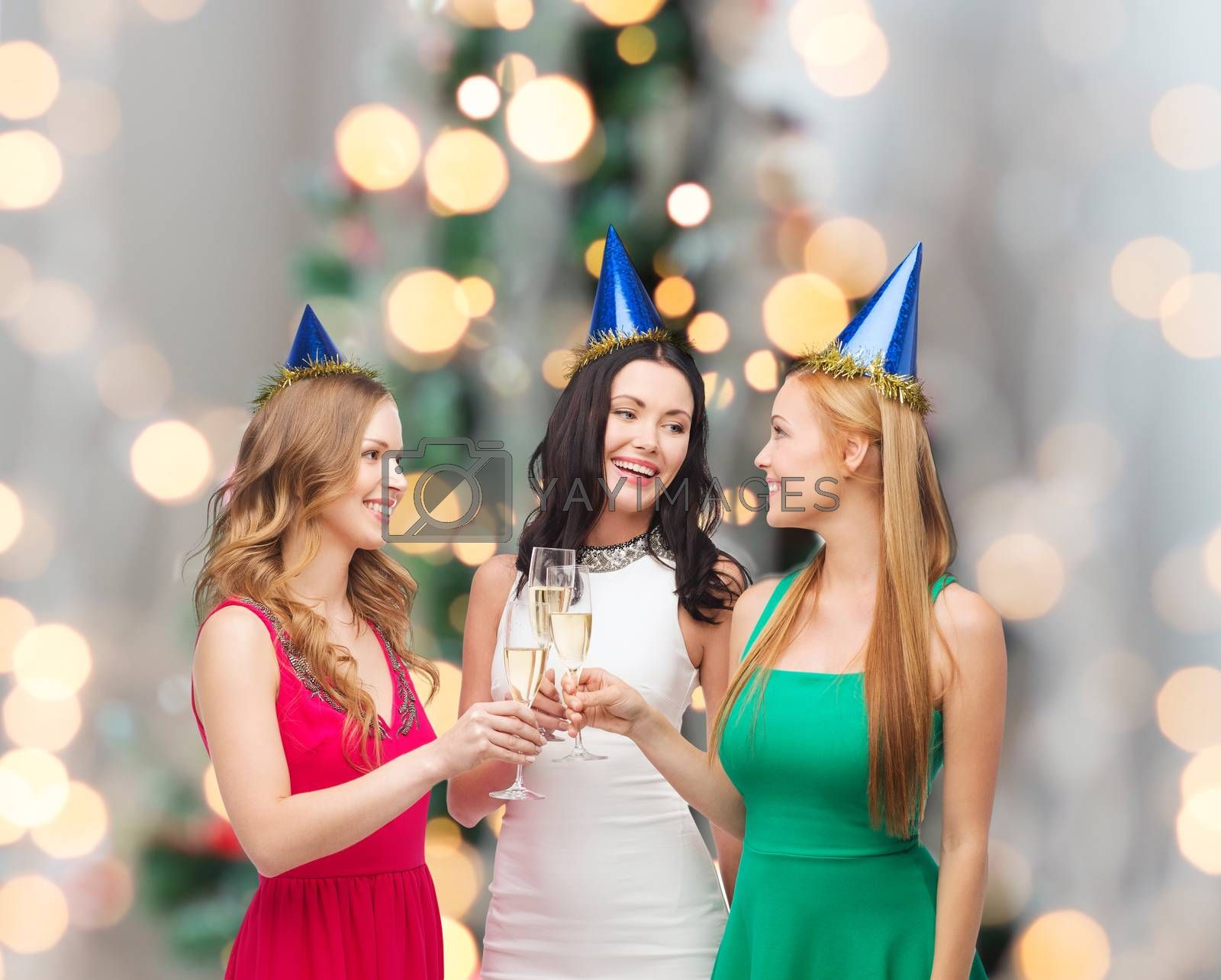 drinks, holidays, people and celebration concept - smiling women in party hats with glasses of sparkling wine over christmas tree lights background
