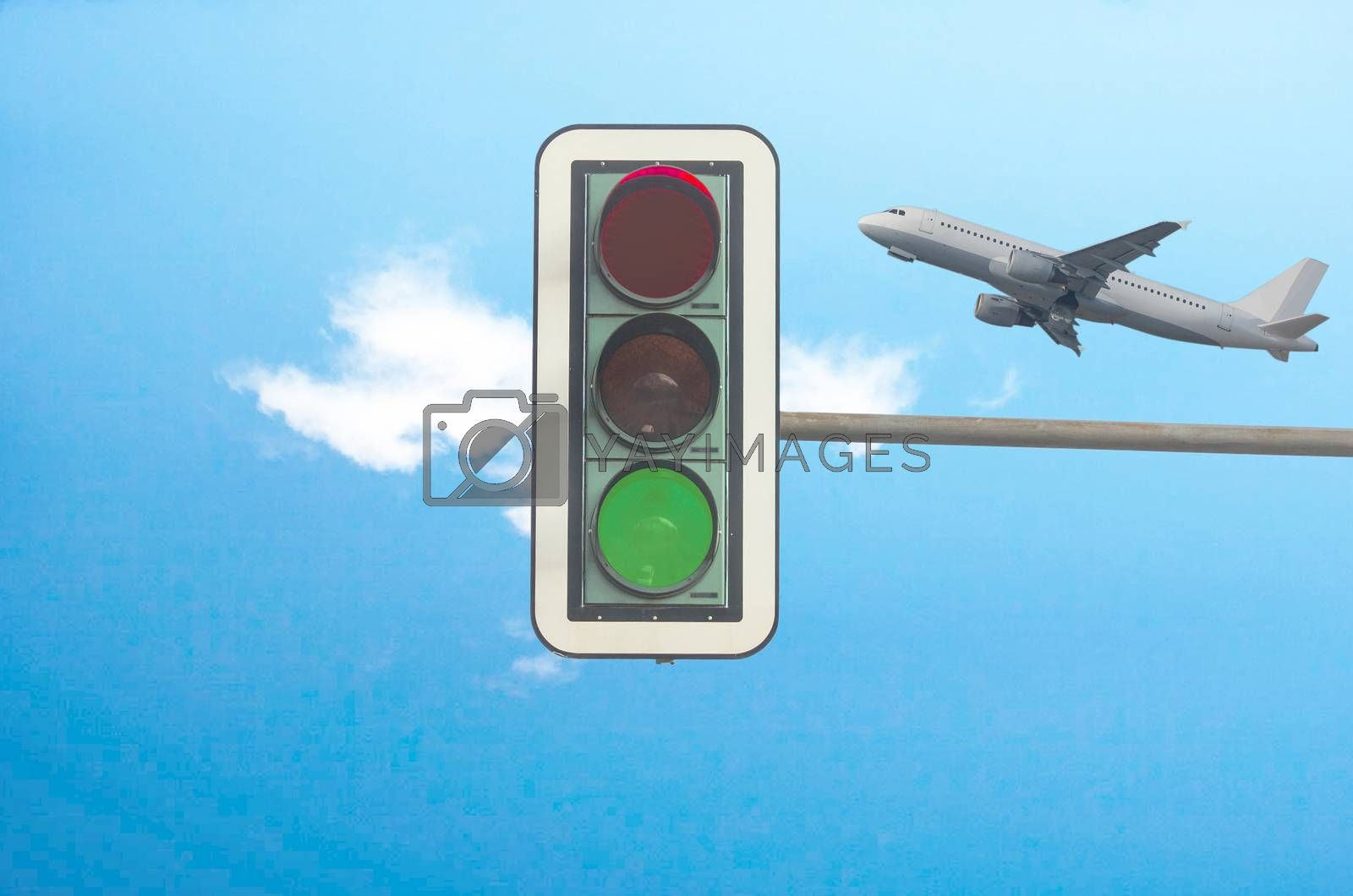 Green color on the traffic light with a beautiful blue sky. In the background, flying a plane.
