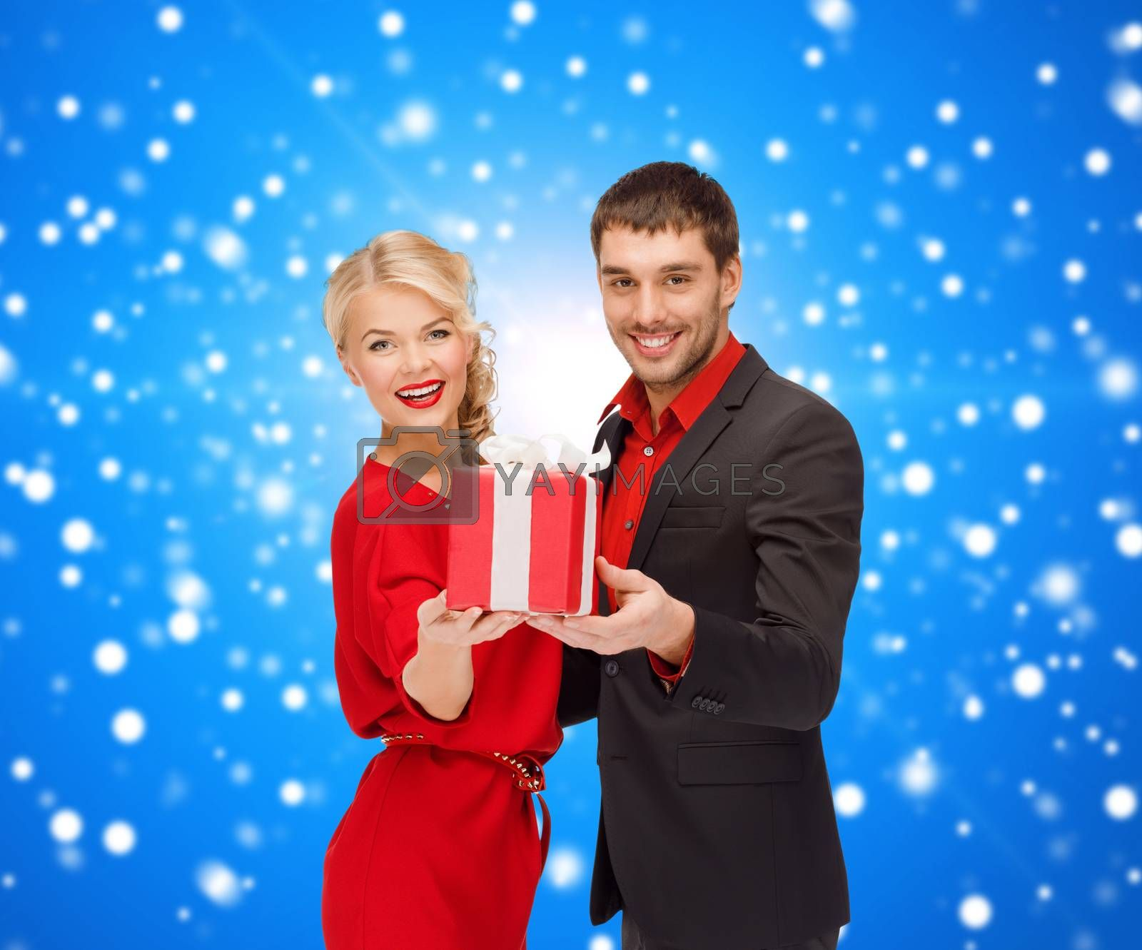 christmas, holidays, valentine's day, celebration and people concept - smiling man and woman with present over blue snowy background