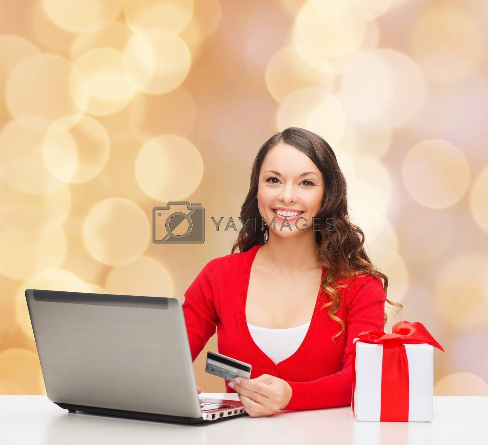 smiling woman with credit card and laptop by dolgachov