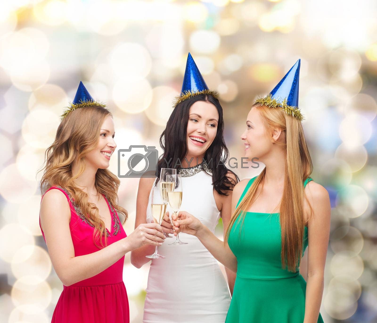 drinks, holidays, people and celebration concept - smiling women in party hats with glasses of sparkling wine over lights background