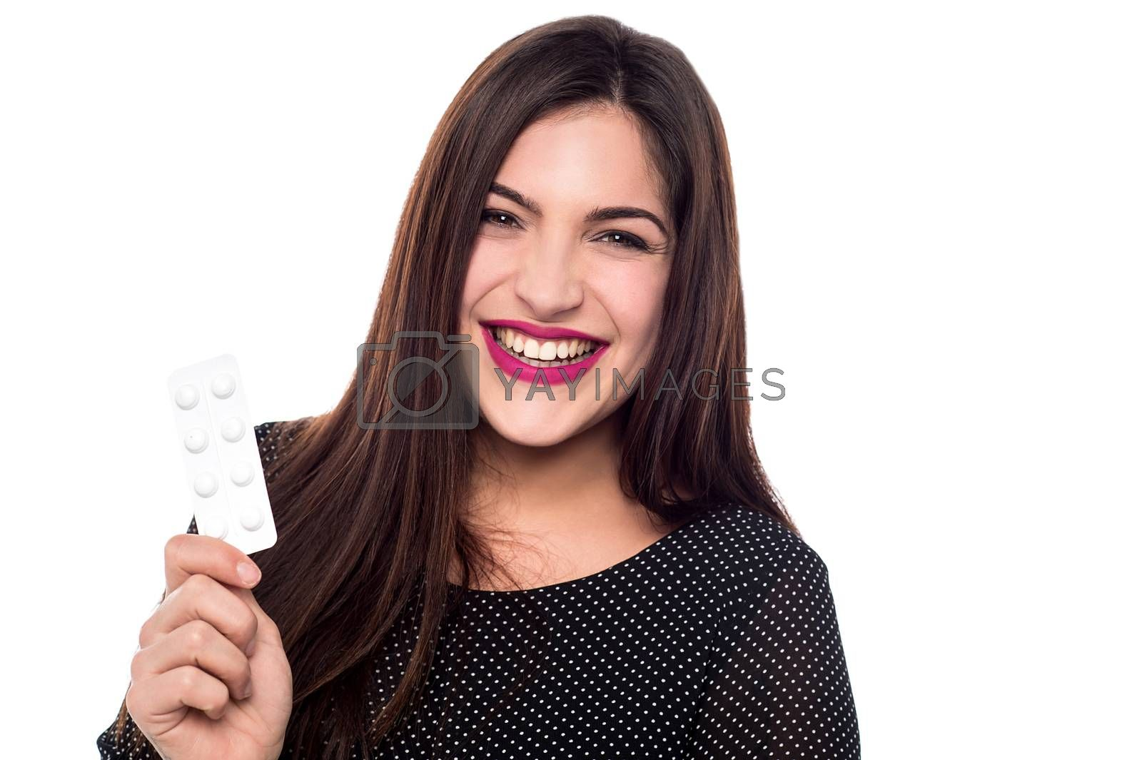Happy young woman showing strip of pills