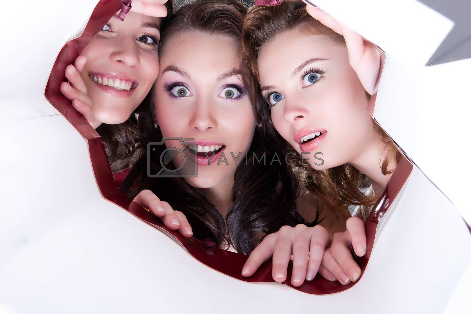 Three young smiling women looking into the paper shopping bag