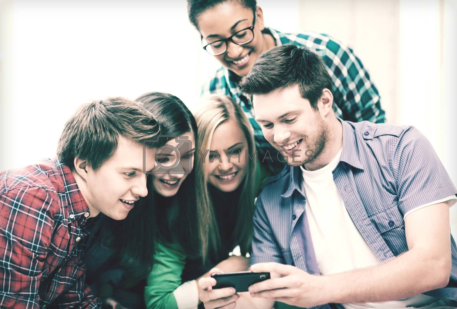 education and technology - group of students looking at smartphone at school