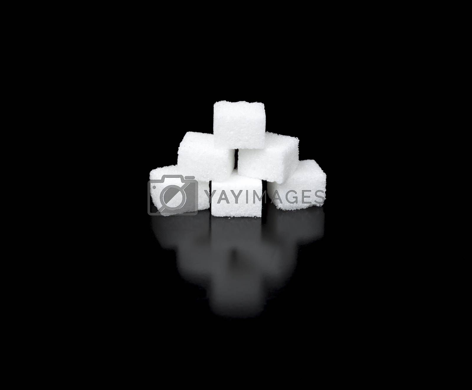 Sugar Cubes in a Pyramid with completely black background and reflection.