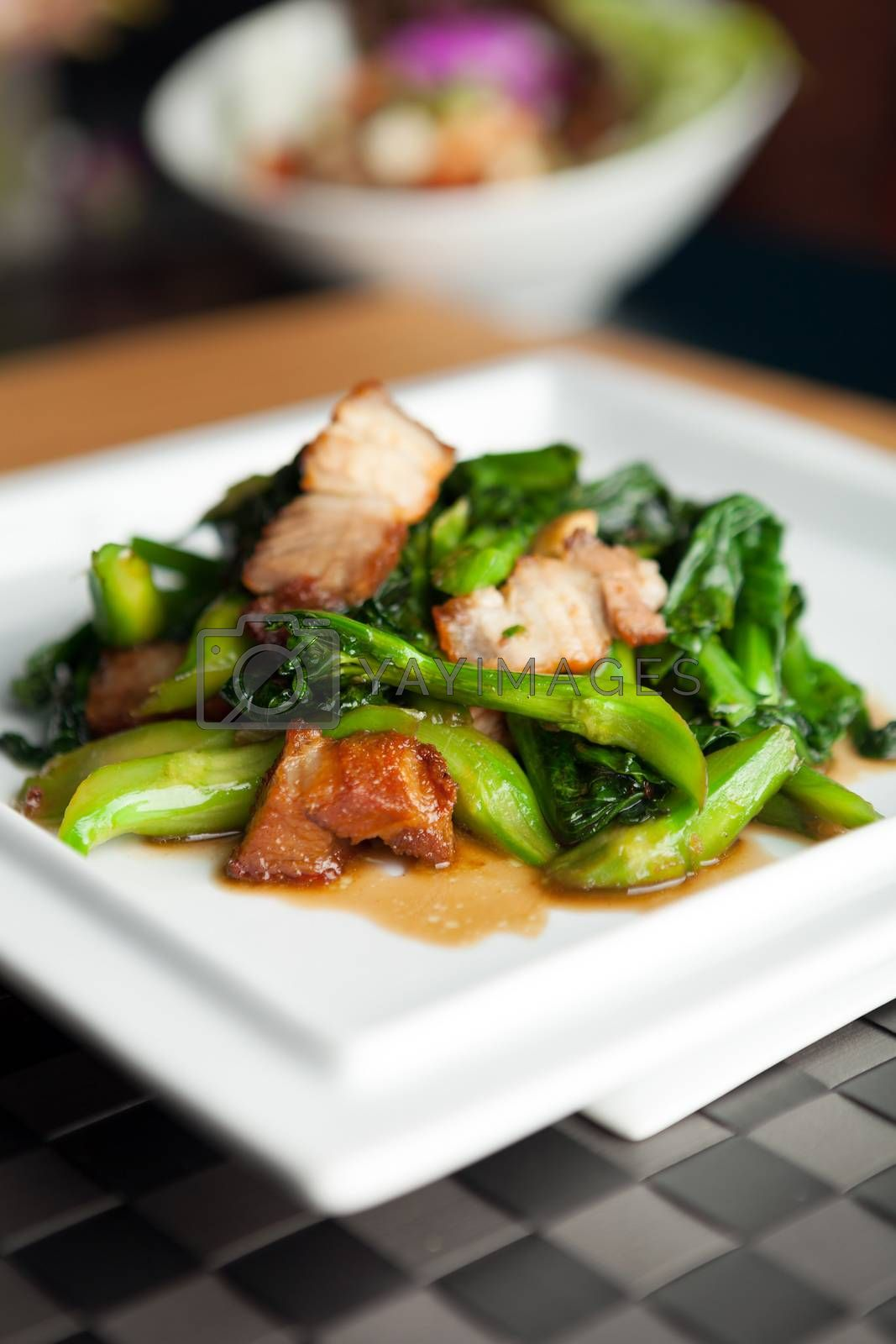 Thai style crispy pork dish with Chinese broccoli.  Shallow depth of field.
