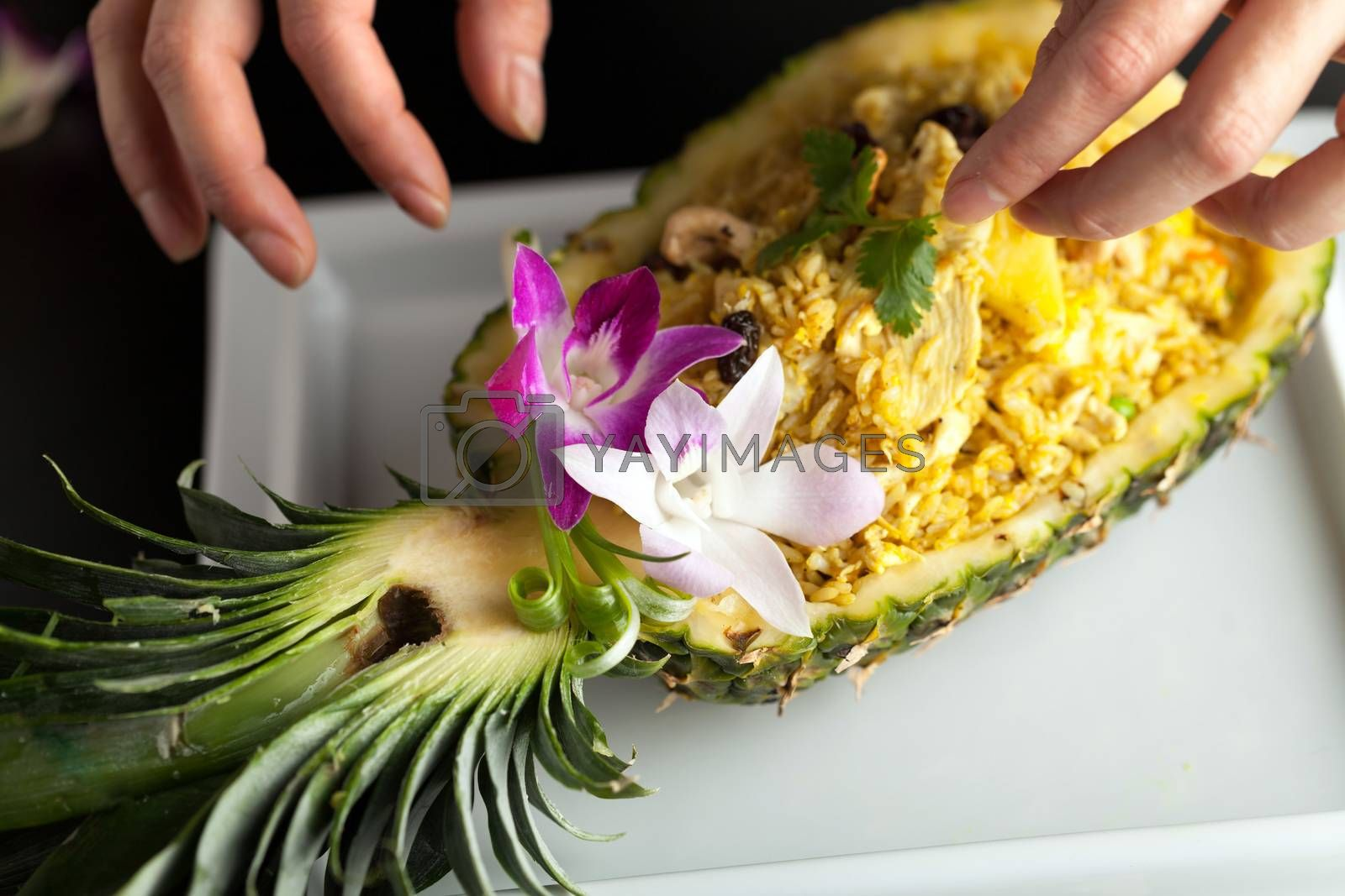 Freshly prepared pineapple fried rice served inside of a pineapple carved like a bowl. Food stylish is arranging garnish.