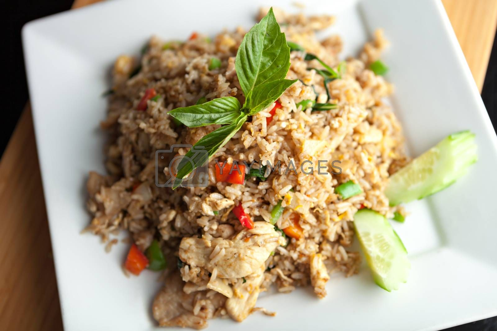 A Thai dish of chicken fried rice presented on a square white plate.  Shallow depth of field.