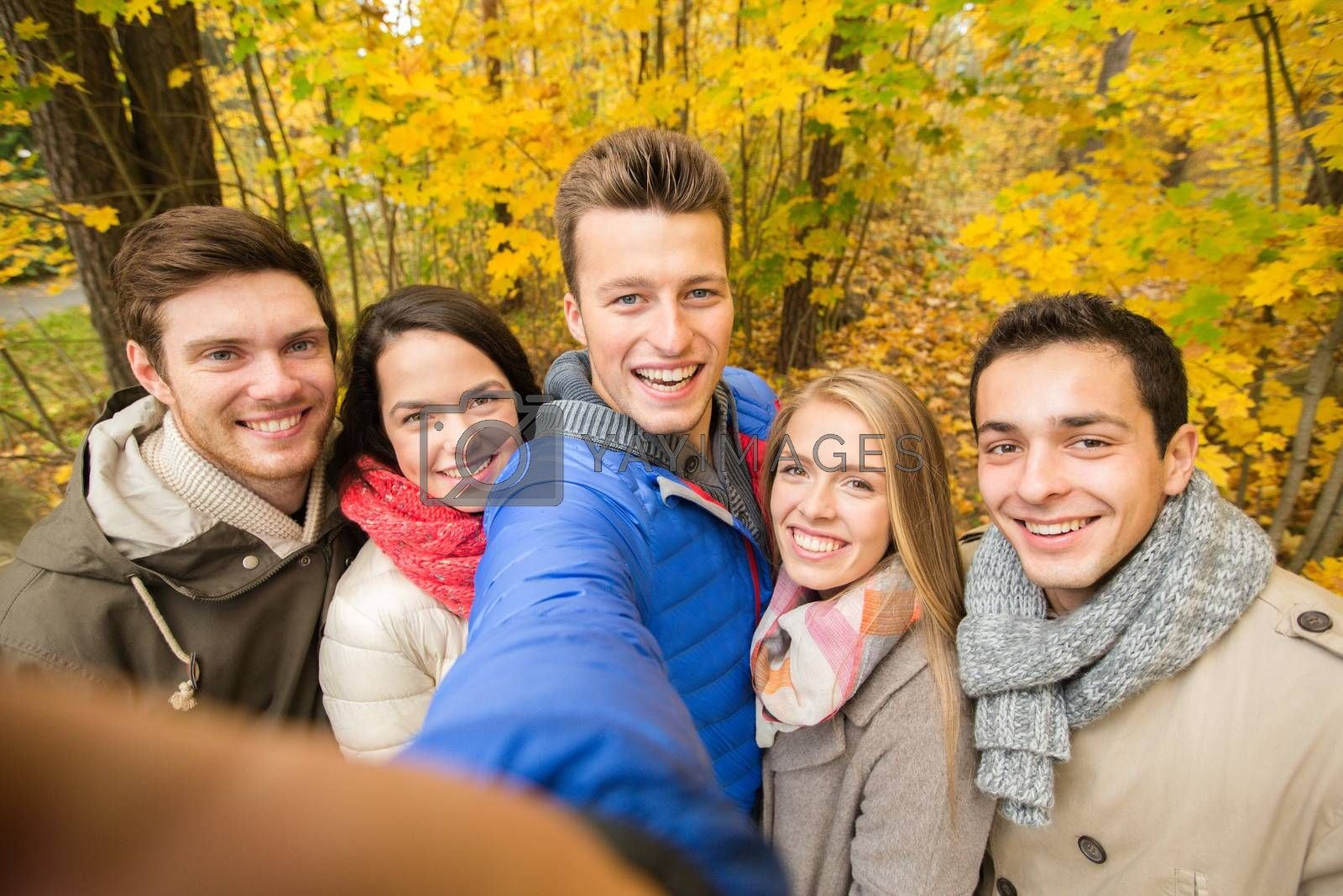 technology, season, friendship and people concept - group of smiling men and women taking selfie with smartphone or camera in autumn park