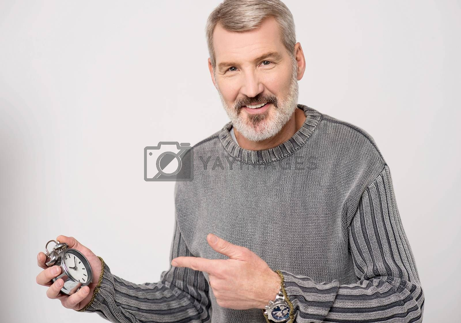 Mature man pointing at an antique time piece