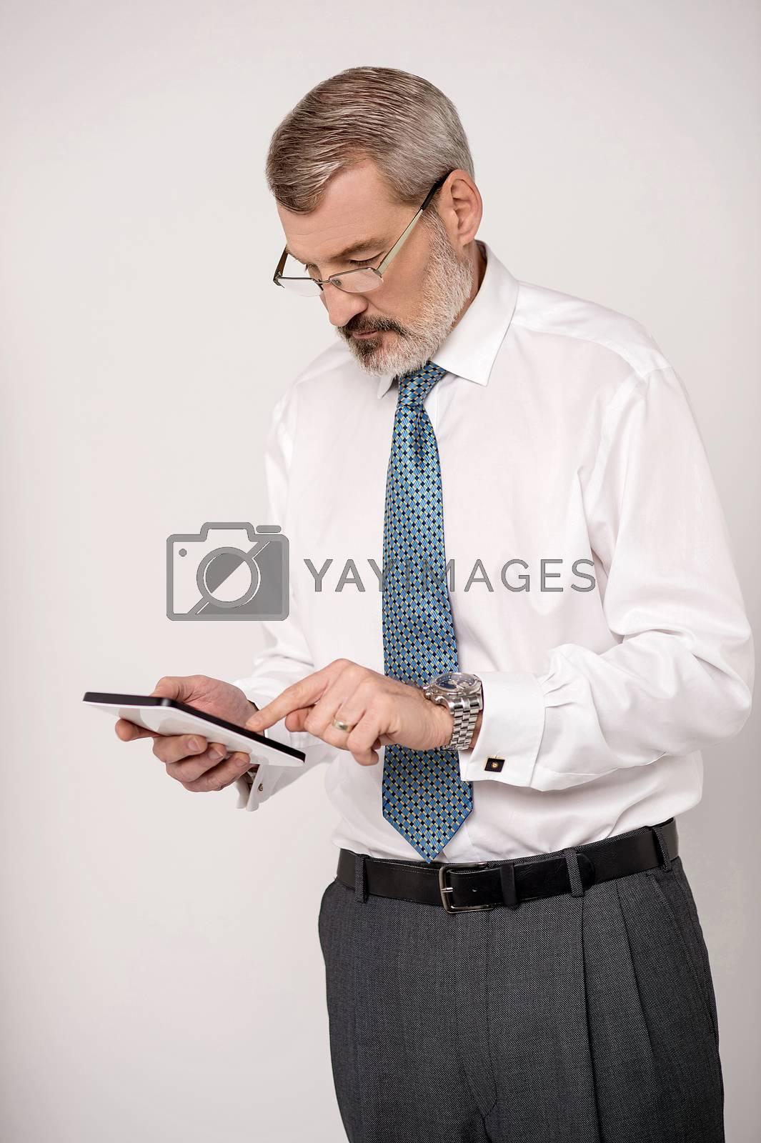 Senior entrepreneur browsing on his tablet pad