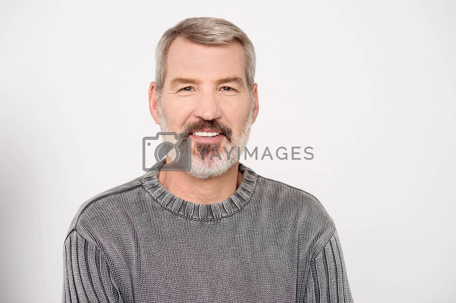 Elderly man posing casually to camera on grey background
