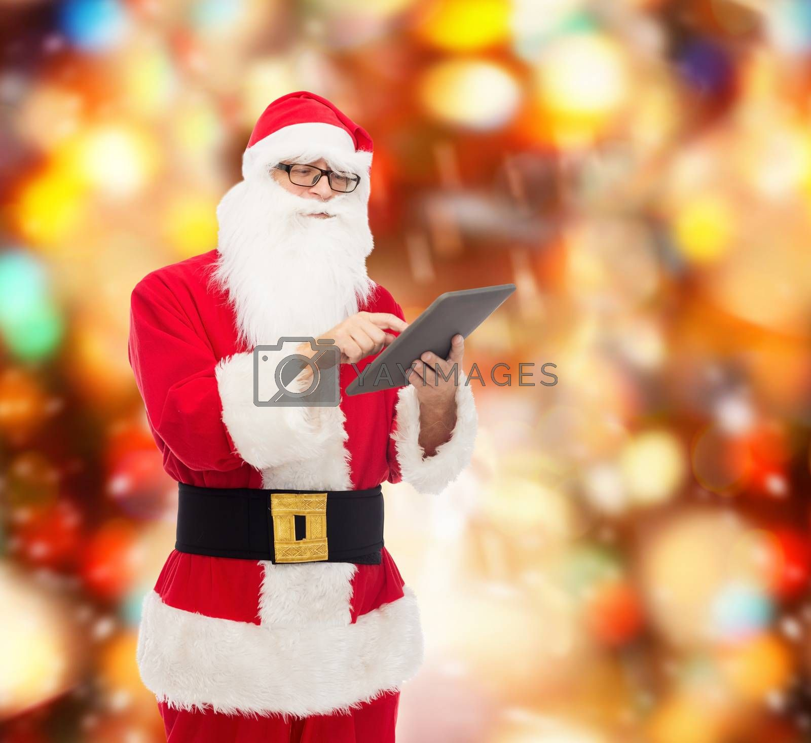 christmas, holidays, technology and people concept - man in costume of santa claus with tablet pc computer over red lights background
