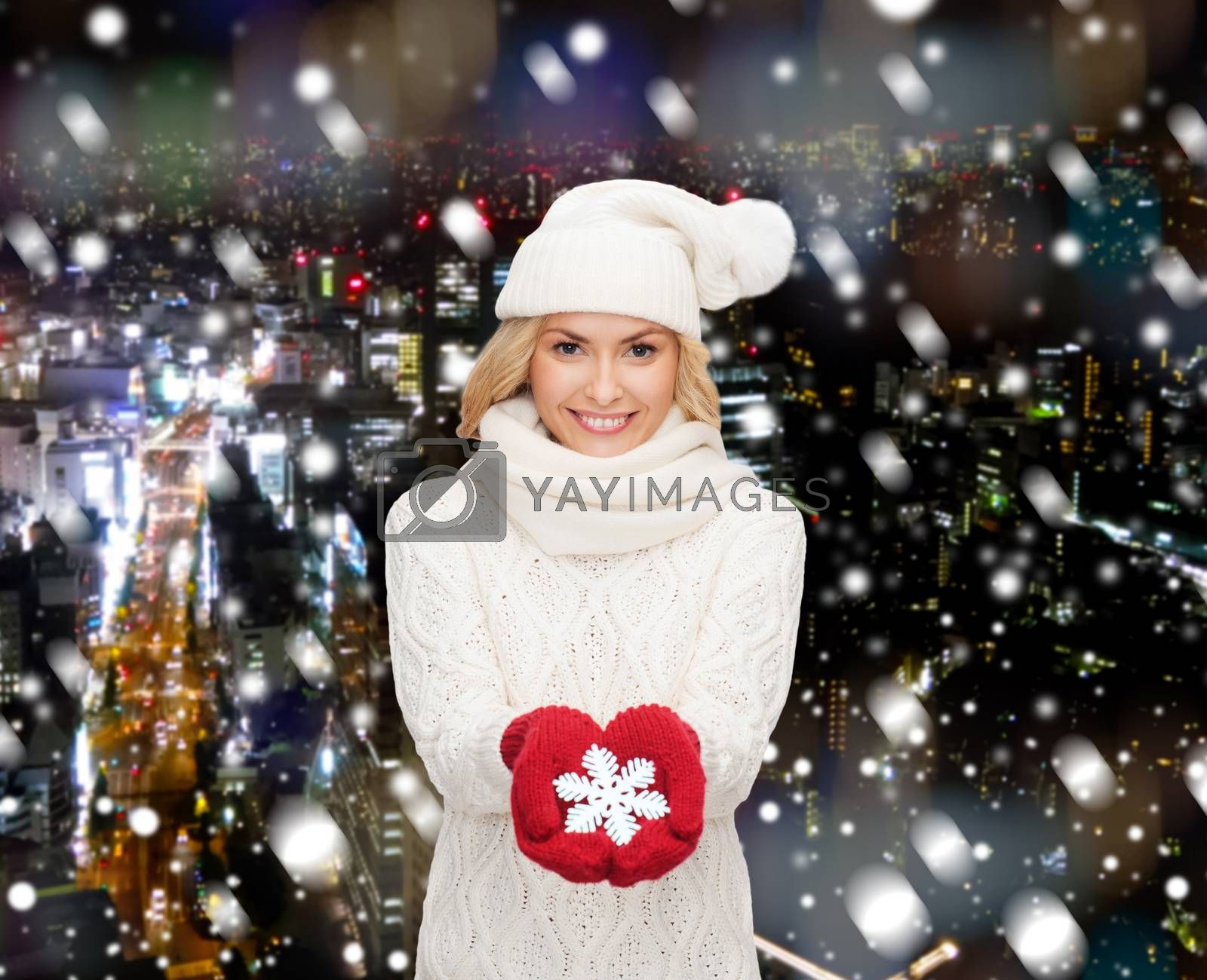 happiness, winter holidays, christmas and people concept - smiling young woman in hat, scarf and mittens holding snowflake decoration over snowy night city background