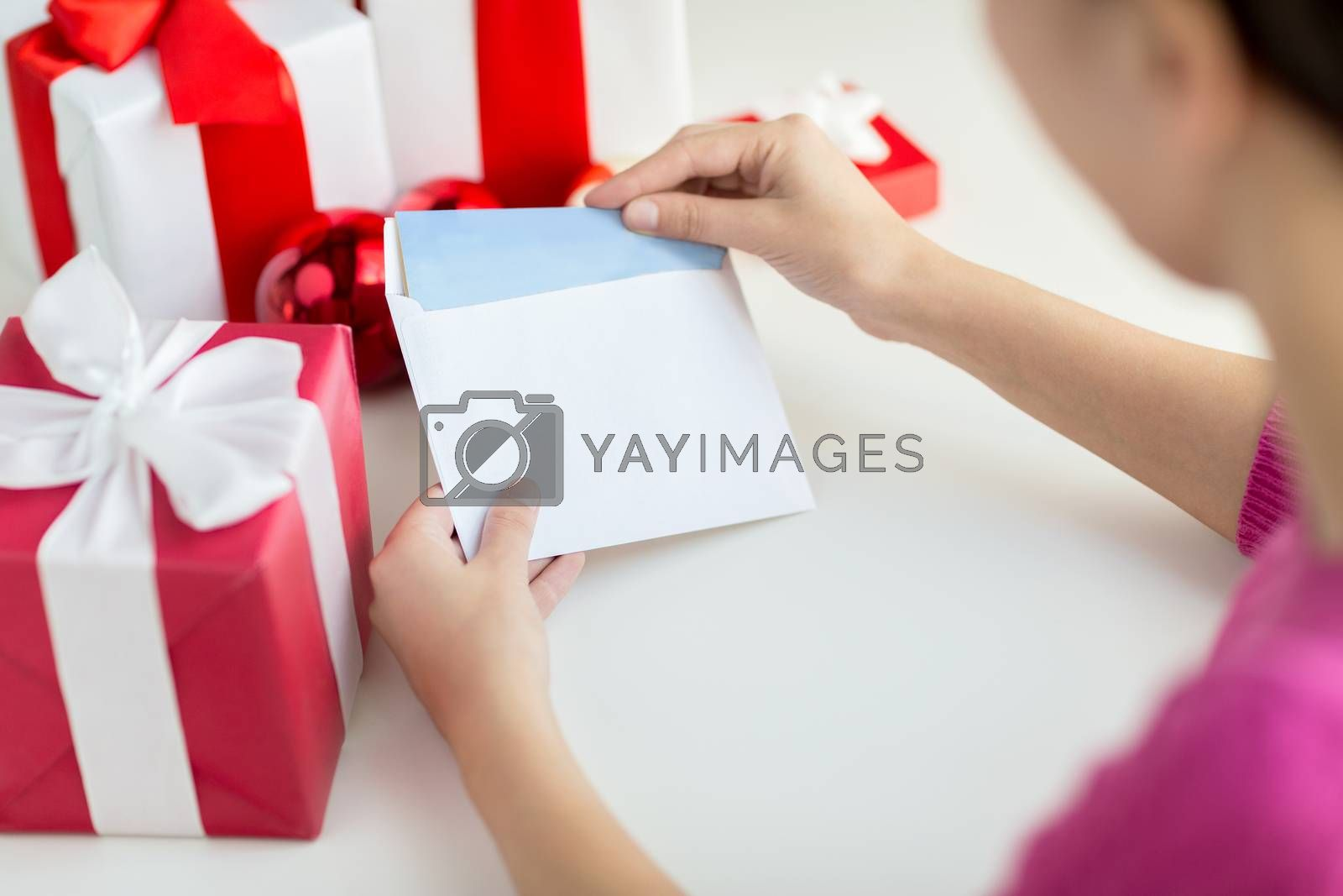 holidays, communication and people concept - close up of woman with letter and presents