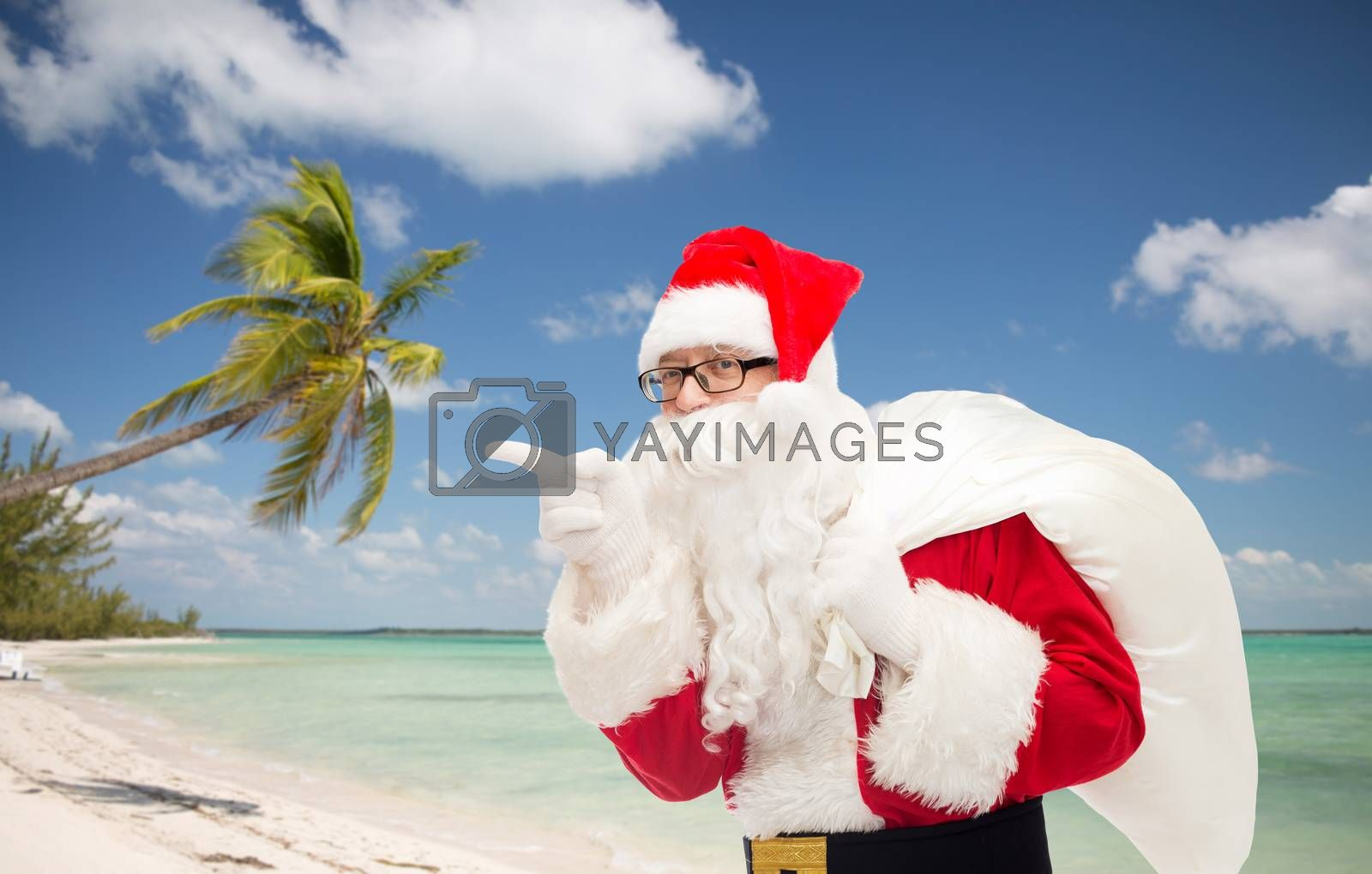 christmas, holidays, travel and people concept - man in costume of santa claus with bag pointing finger over tropical beach background