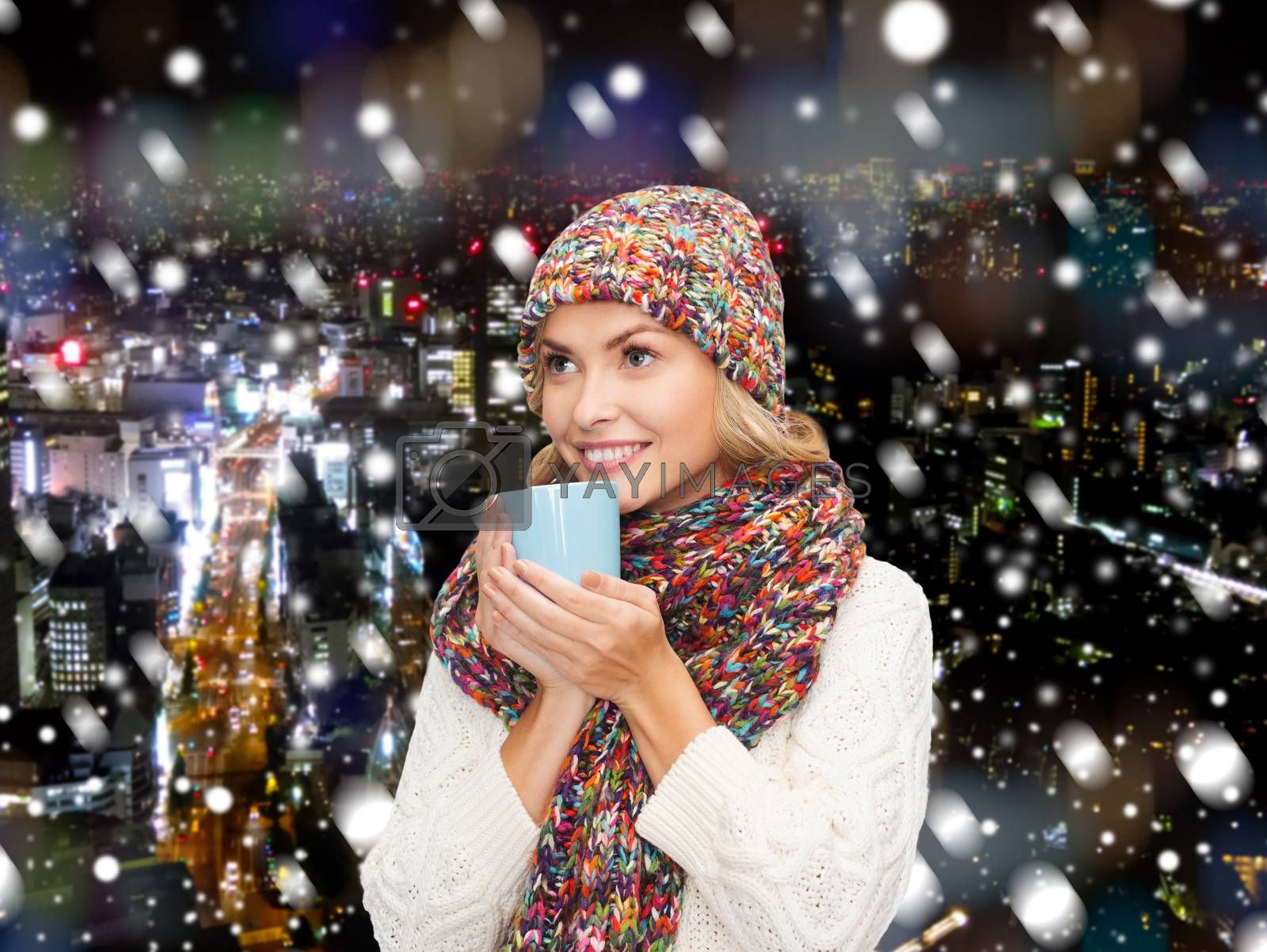 happiness, winter holidays, christmas, beverages and people concept - smiling young woman in warm clothes with cup over snowy city background