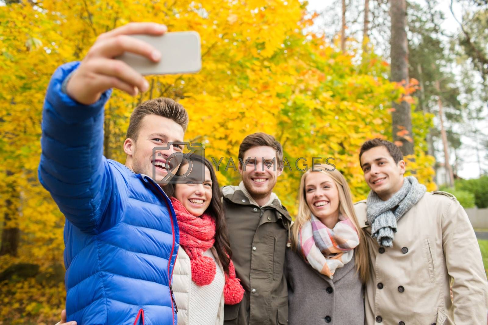 season, people, technology and friendship concept - group of smiling friends with smartphone taking selfie in autumn park
