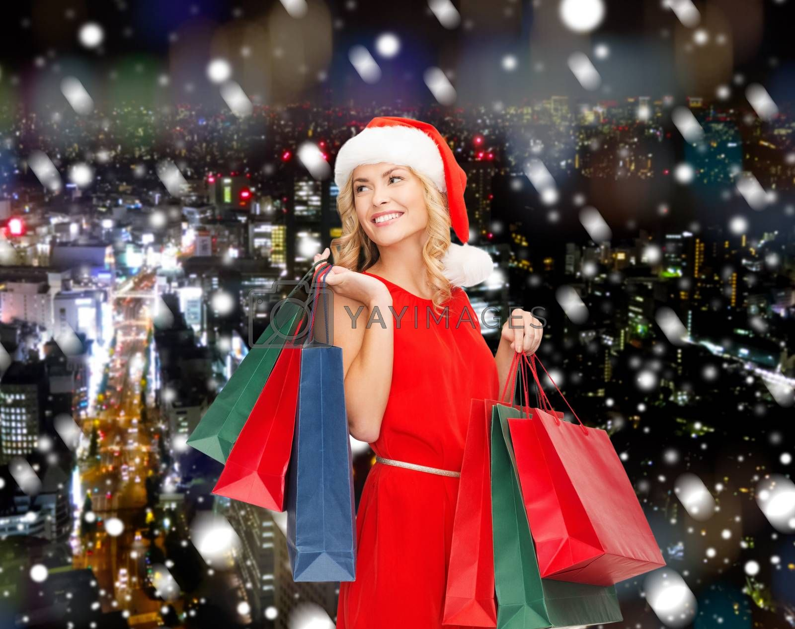 sale, gifts, christmas, holidays and people concept - smiling woman in red dress and santa helper hat with shopping bags over snowy night city background