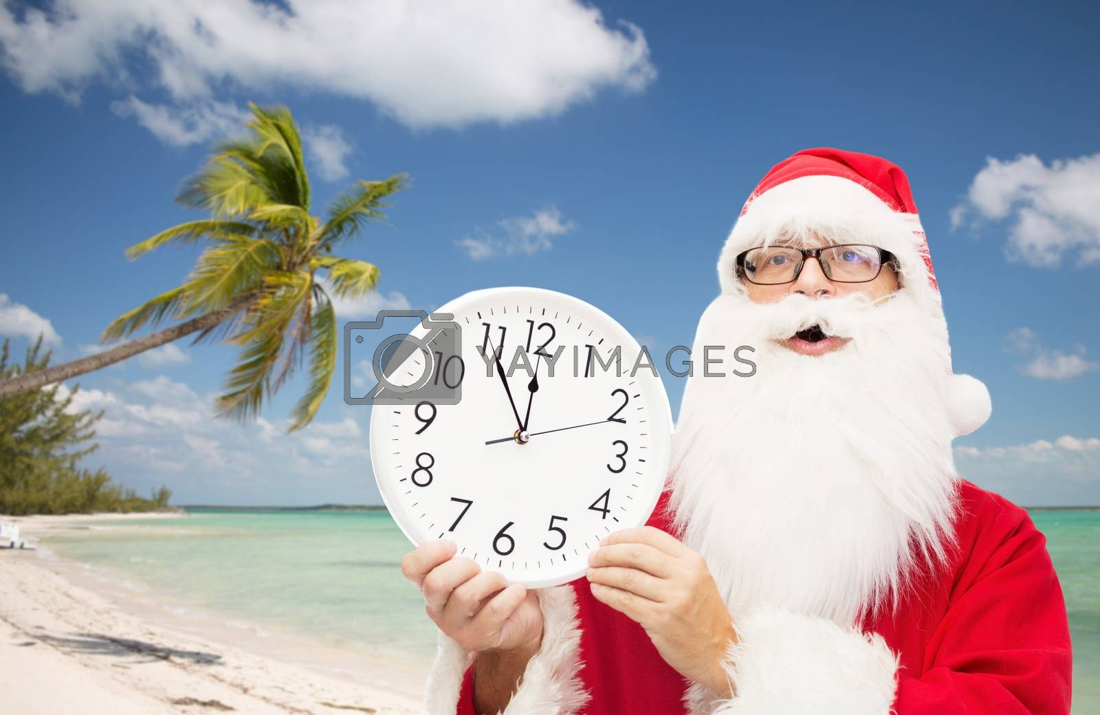 christmas, holidays, travel and people concept - man in costume of santa claus with clock showing twelve over tropical beach background