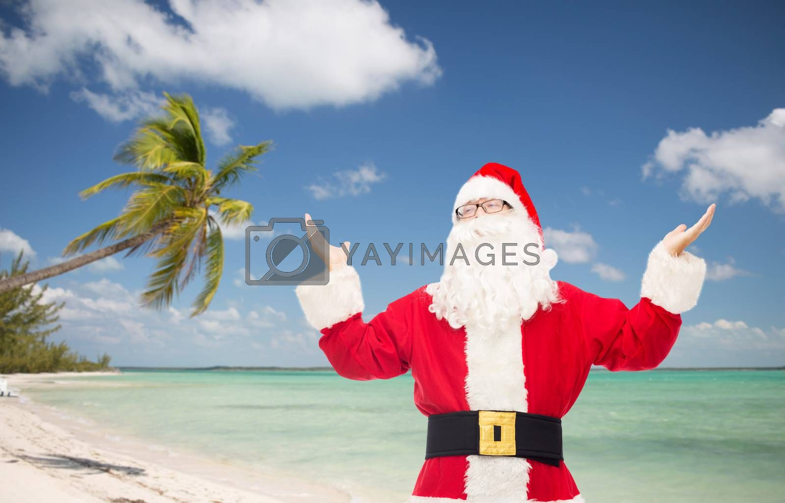 christmas, holidays, travel and people concept - man in costume of santa claus with raised hands over tropical beach background