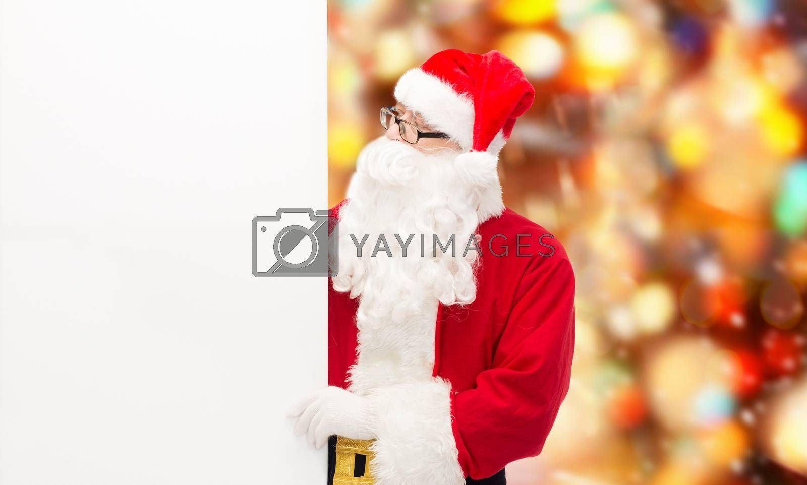 christmas, holidays, advertisement and people concept - man in costume of santa claus with white blank billboard over red lights background