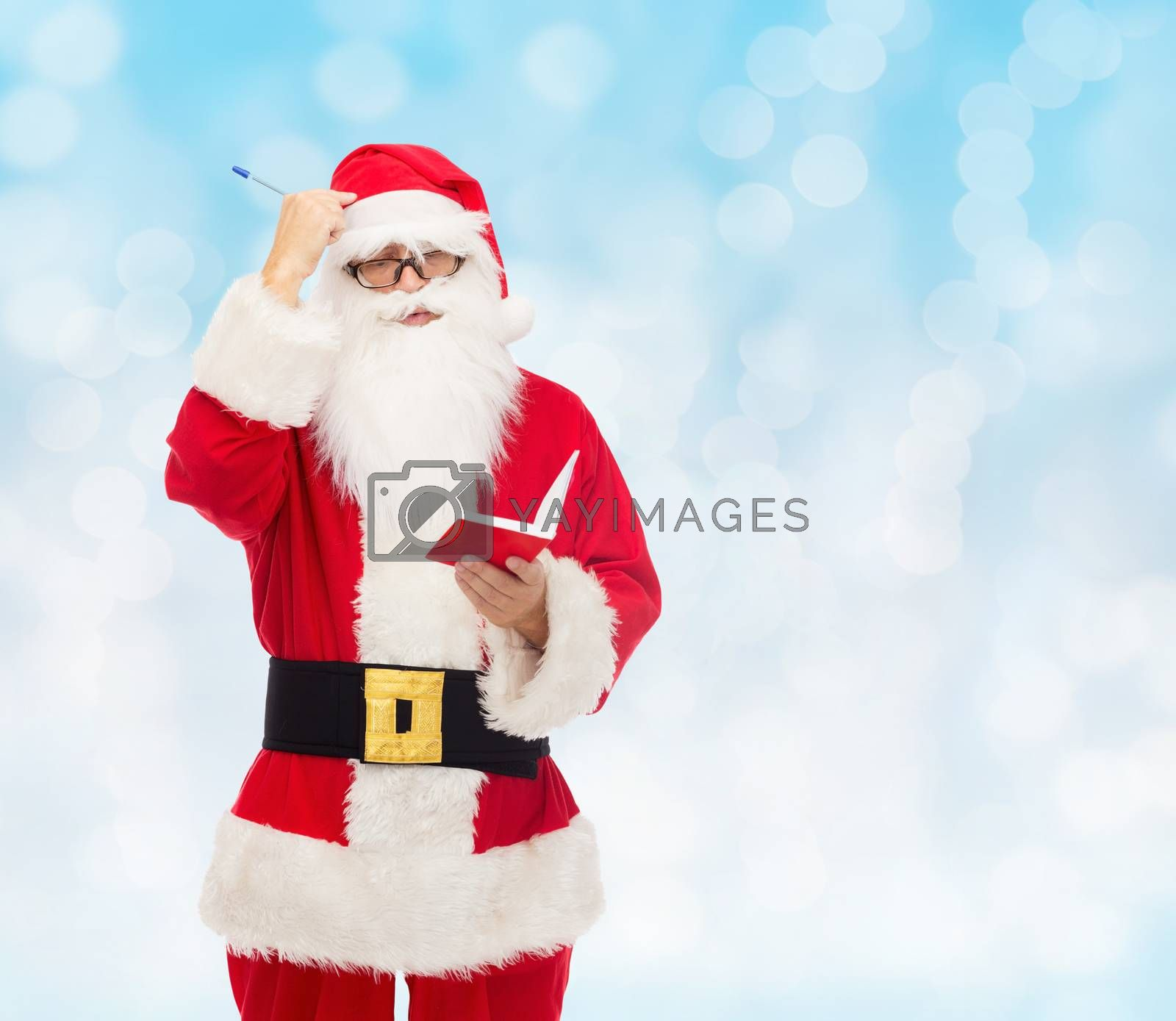 christmas, holidays and people concept - man in costume of santa claus with notepad and pen over blue lights background