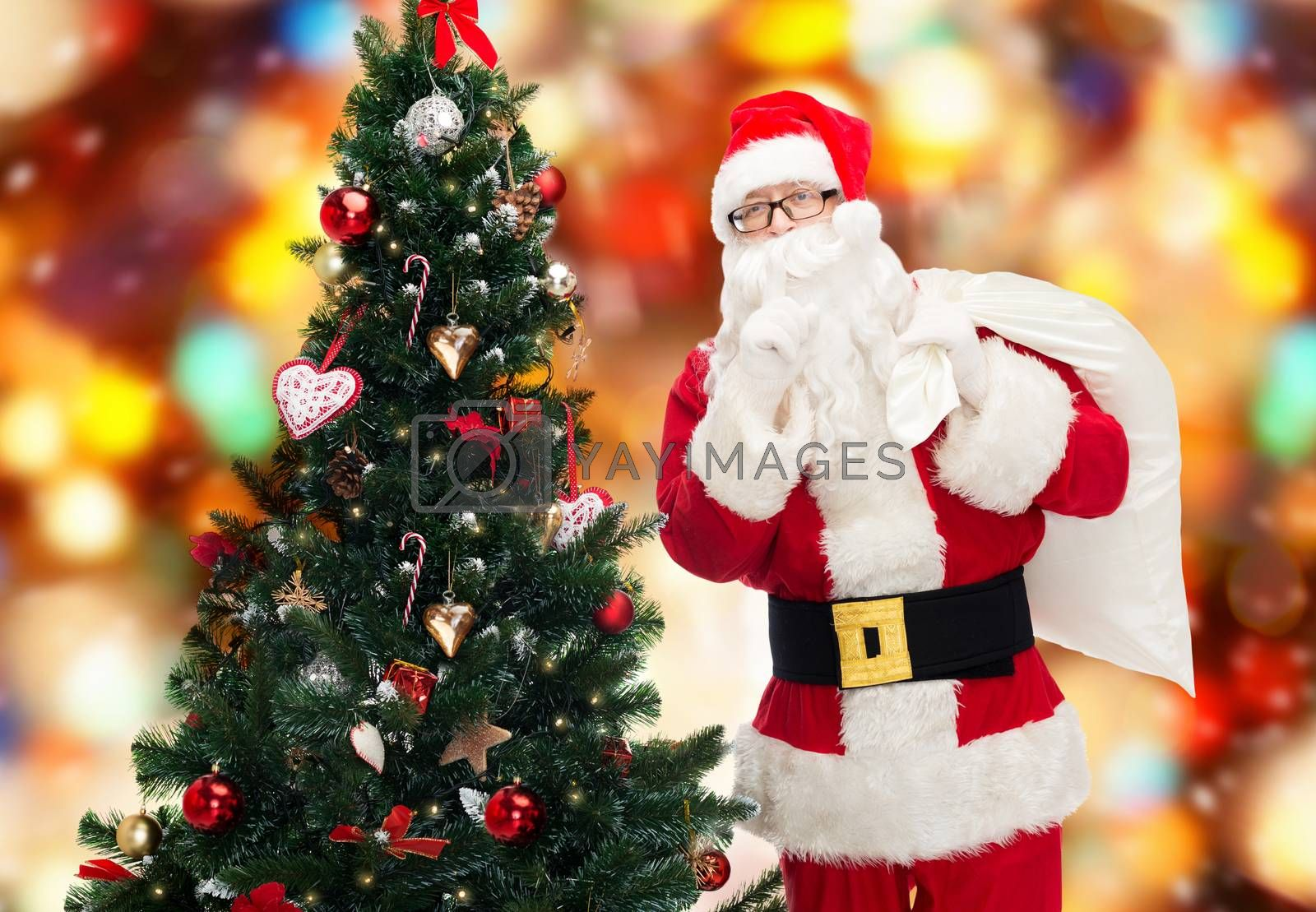 christmas, holidays and people concept - man in costume of santa claus with bag and christmas tree making hush gesture over red lights background