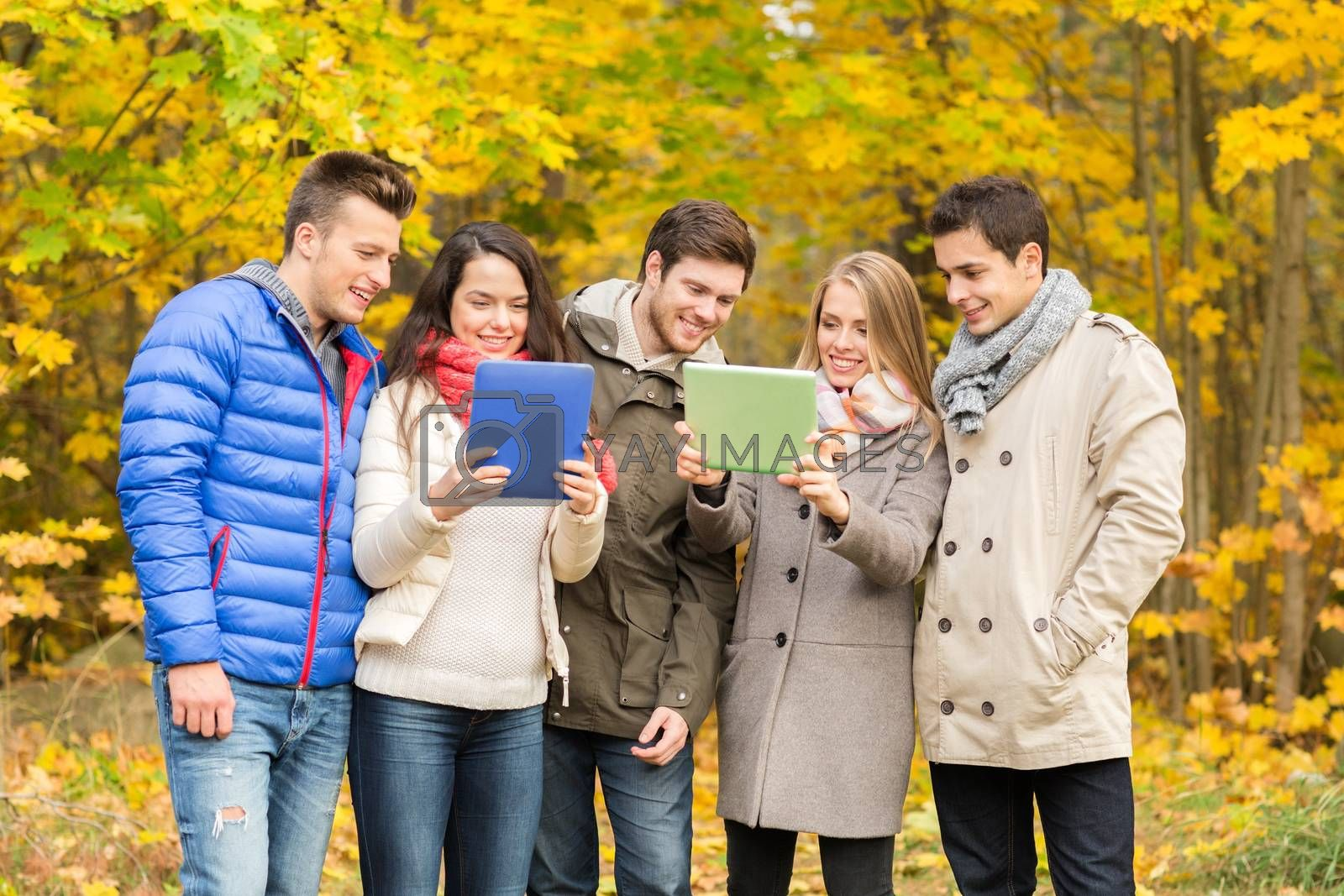 technology, season, friendship and people concept - group of smiling men and women with tablet pc computers in autumn park