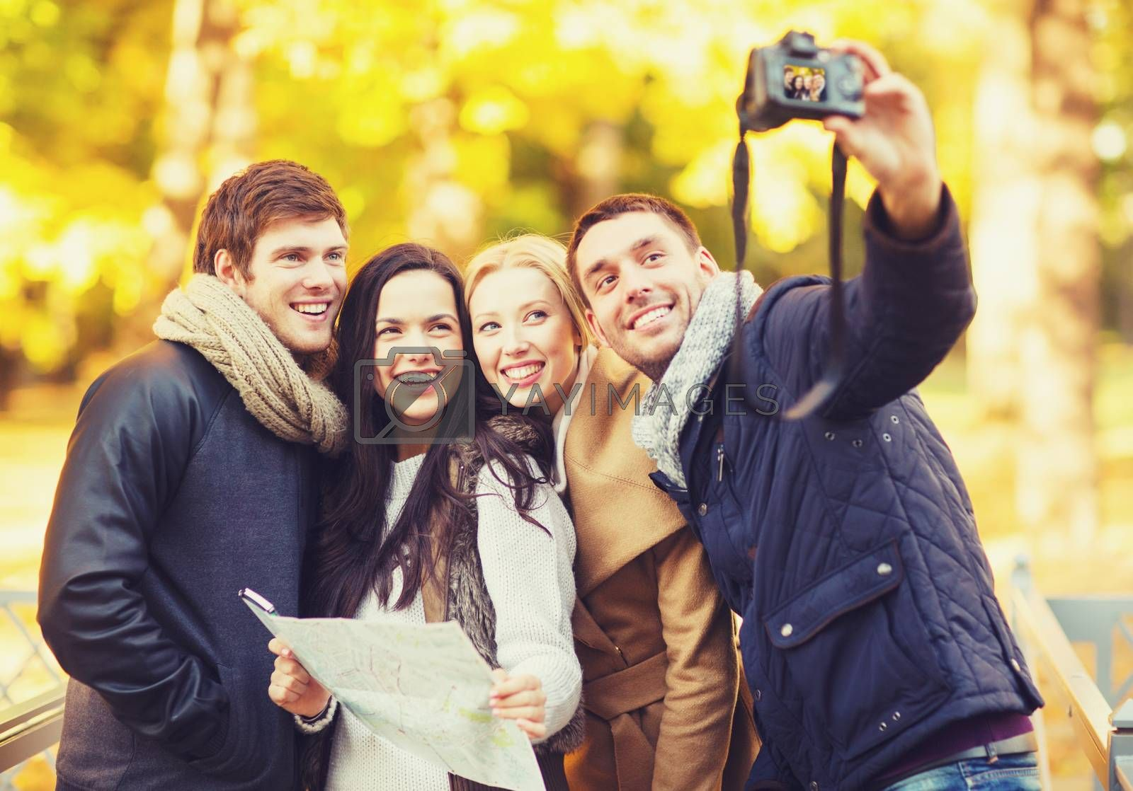technology, holidays, travel, happy people concept - group of friends or couples having fun with photo camera in autumn park