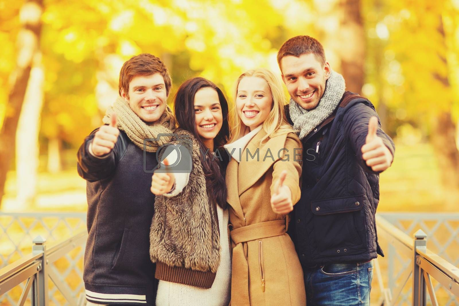 summer, holidays, vacation, happy people concept - group of friends or couples having fun and showing thumbs up in autumn park