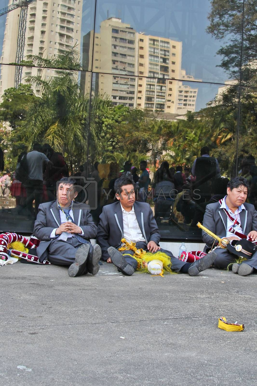 SAO PAULO, BRAZIL August 9 2015: An unidentified group of men resting after the Morenada parade in Bolivian Independence Day celebration in Sao Paulo Brazil.
