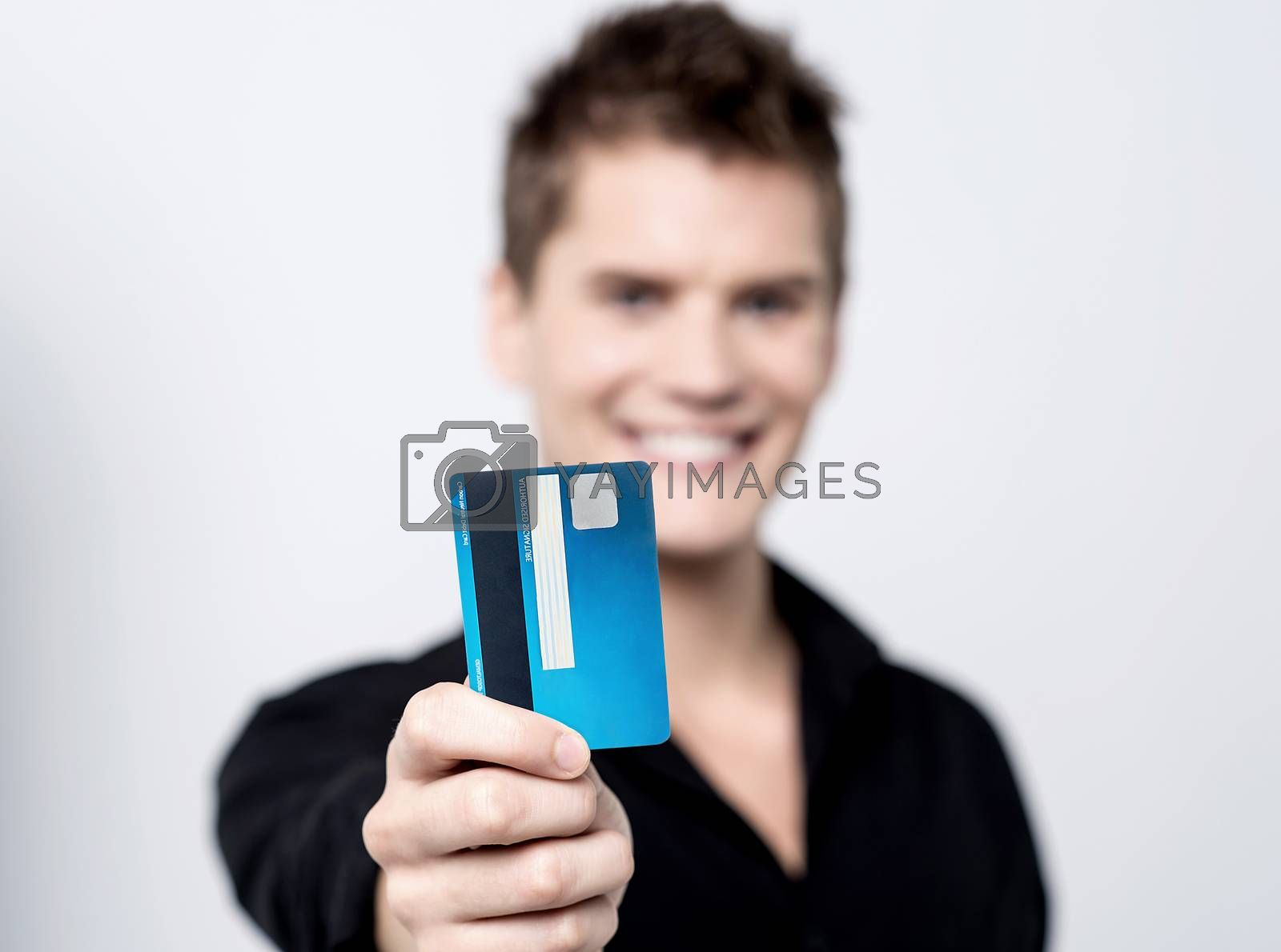 Young male showing his credit card to camera