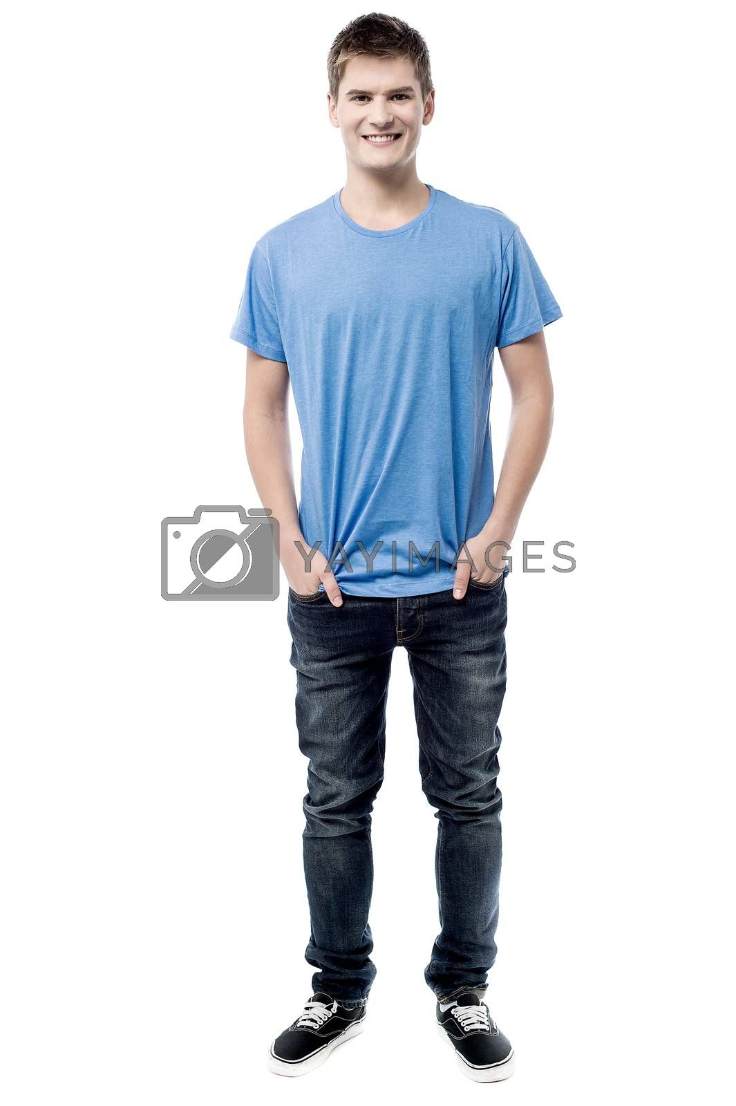 Smiling man posing with hands in pockets
