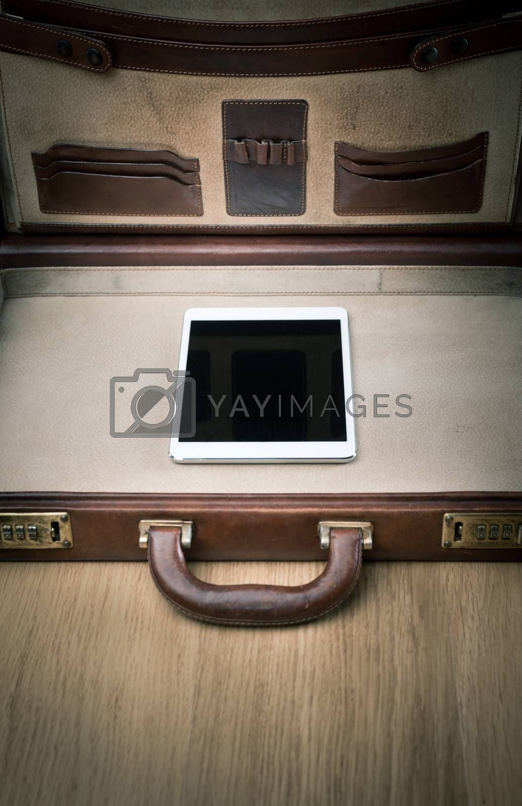 Open leather brefcase on parquet with only digital tablet inside.