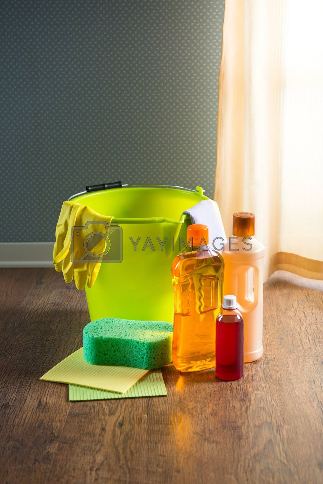Wood cleaners and detergents on floor with bucket, gloves, cloth and sponges.