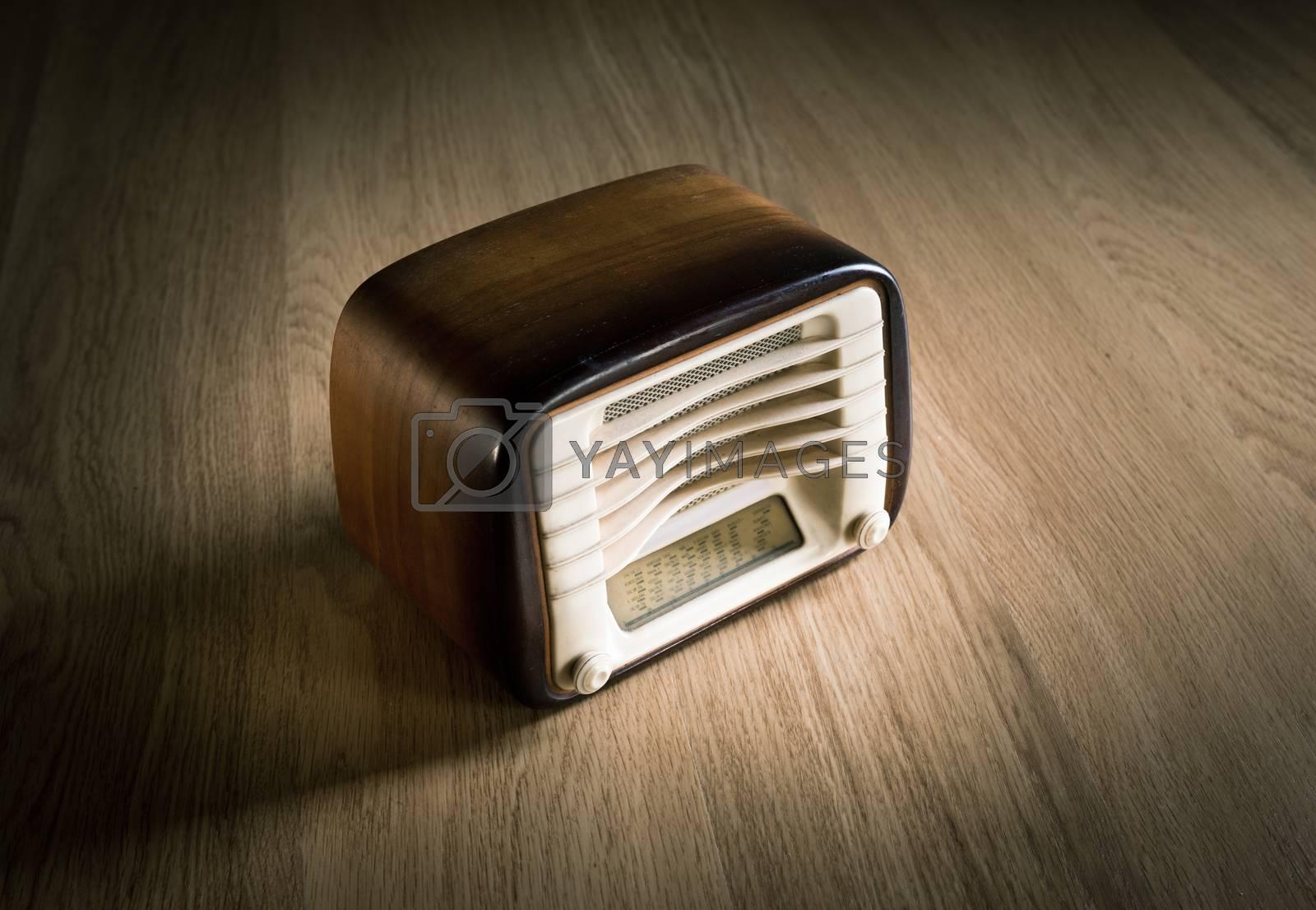 Vintage shiny wooden radio on a wooden desk.