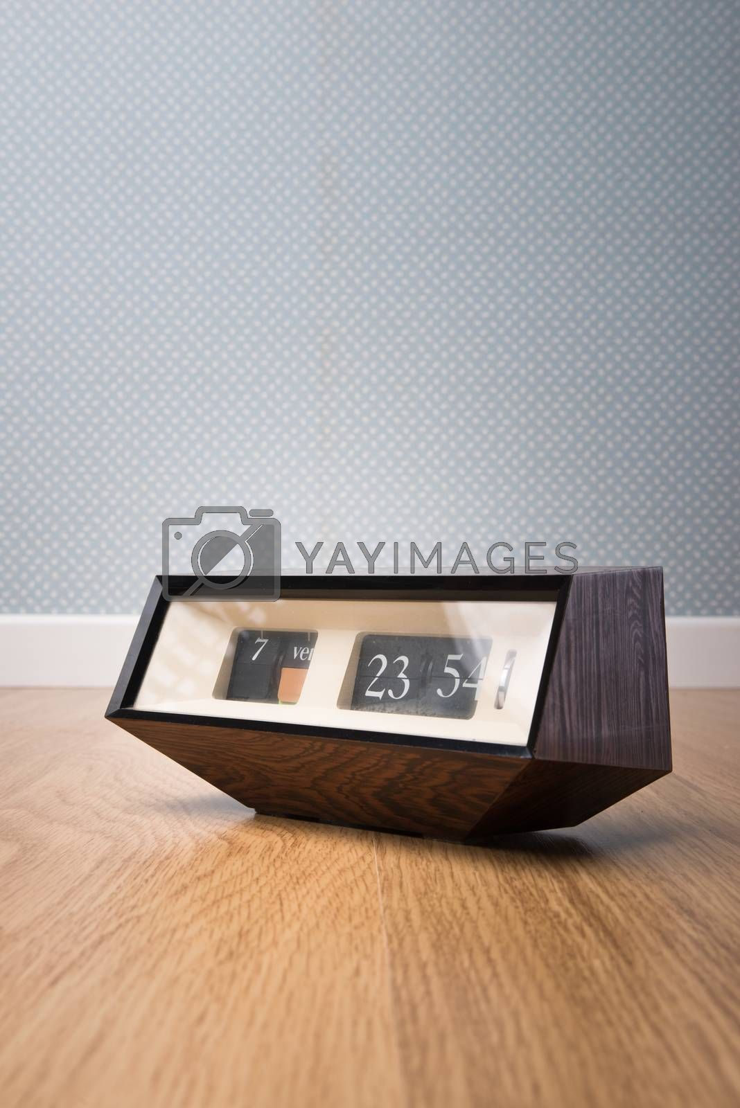 Vintage edgy clock on wooden surface with vintage dotted wallpaper on background.